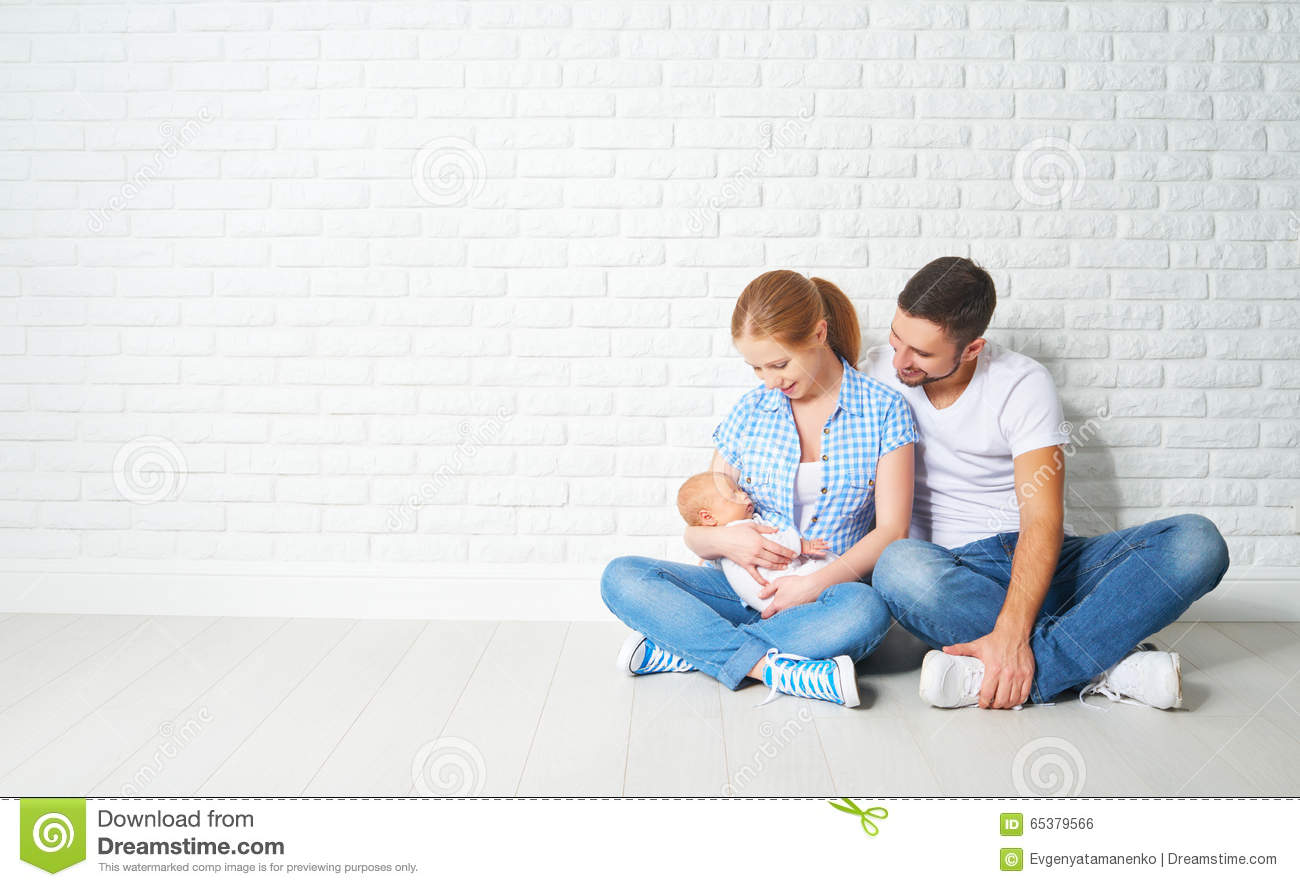 happy family mother, father of a newborn baby on floor near blank wall
