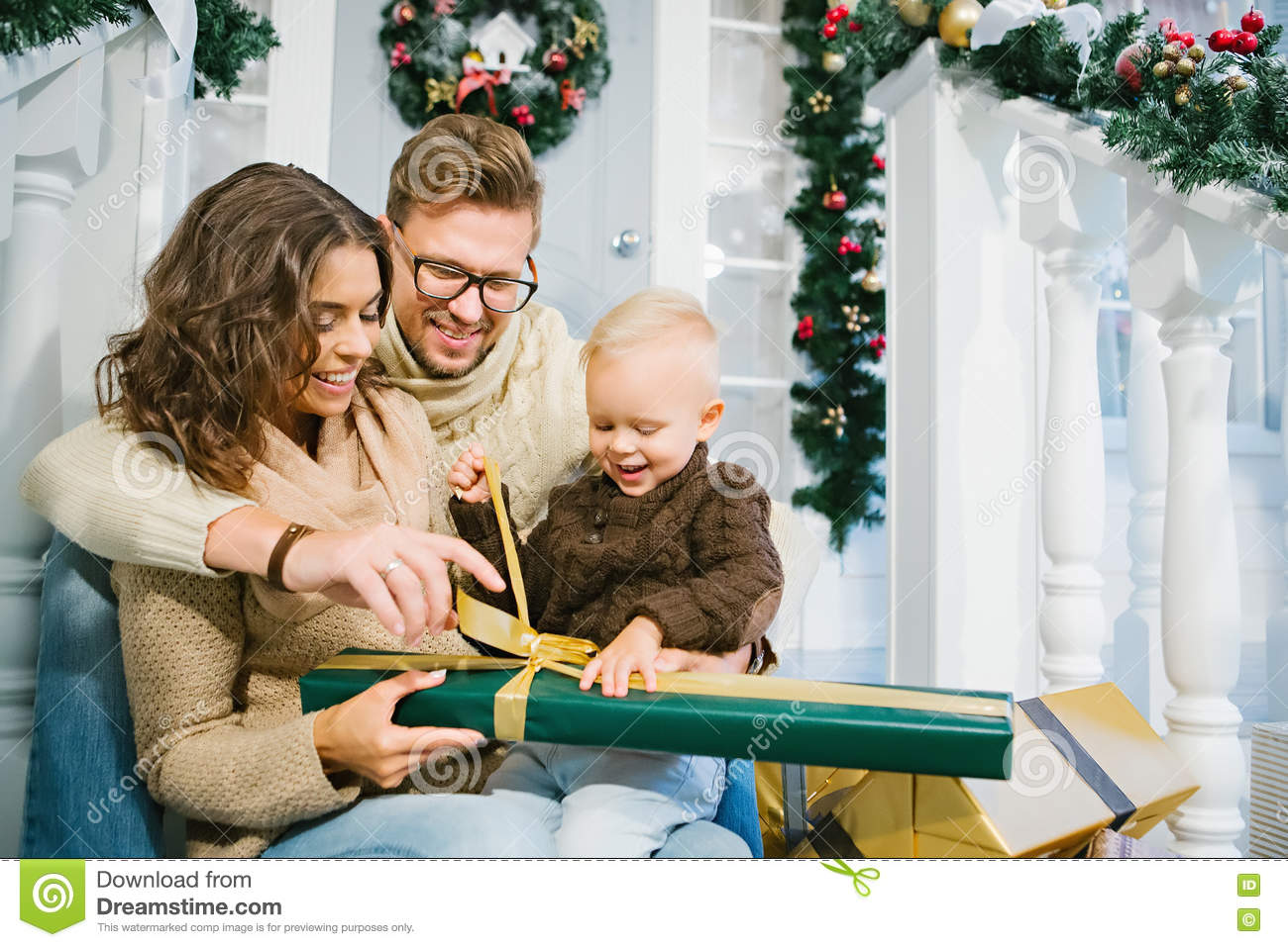 Happy family - mother, father and son unpack the Christmas gifts