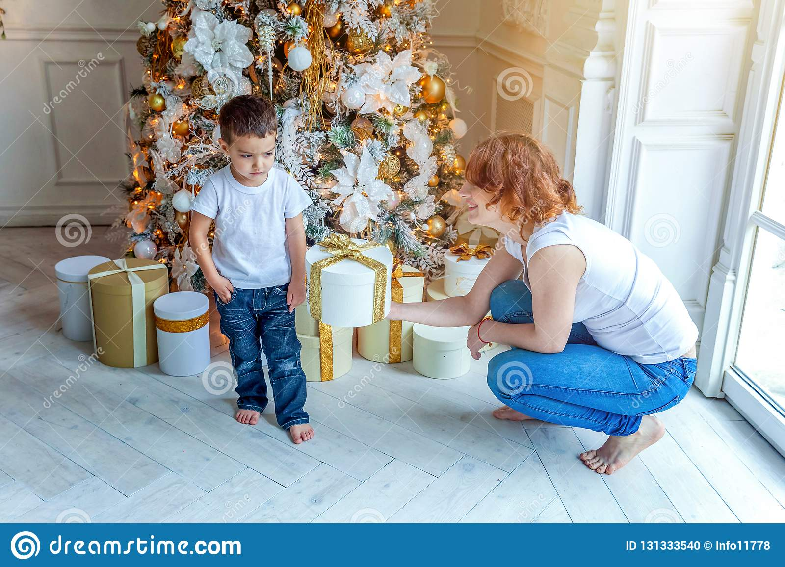 Mother and son near Christmas tree at home