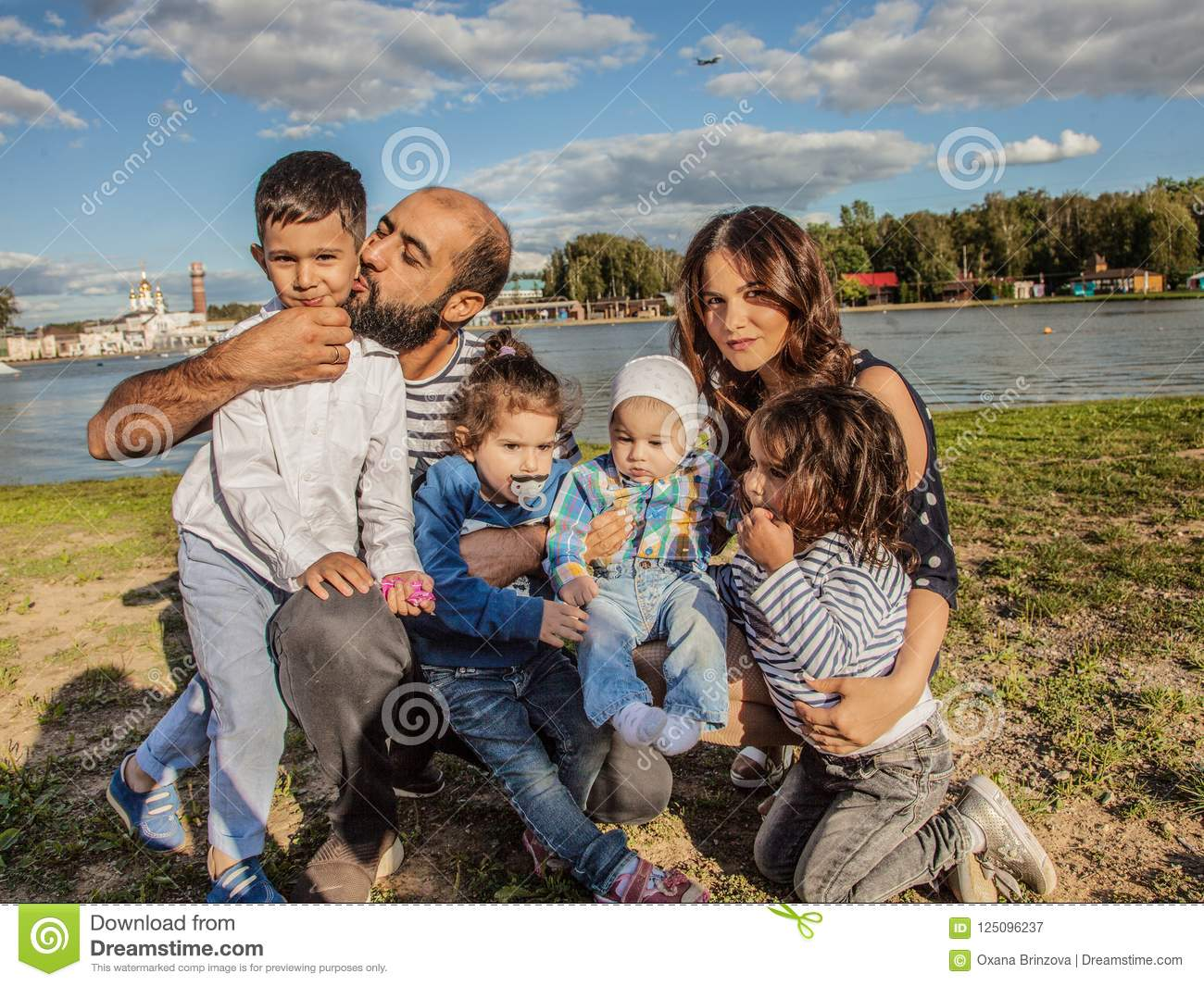 Happy family in nature on the background of a beautiful lake. Mom dad two daughters and two sons.