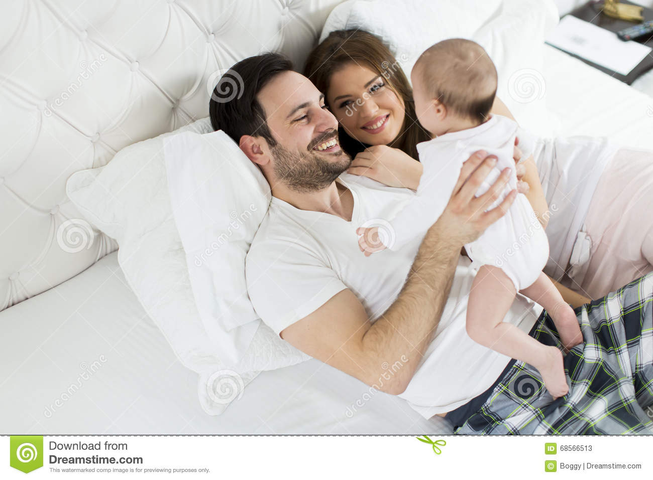 Happy family with newborn baby in bed