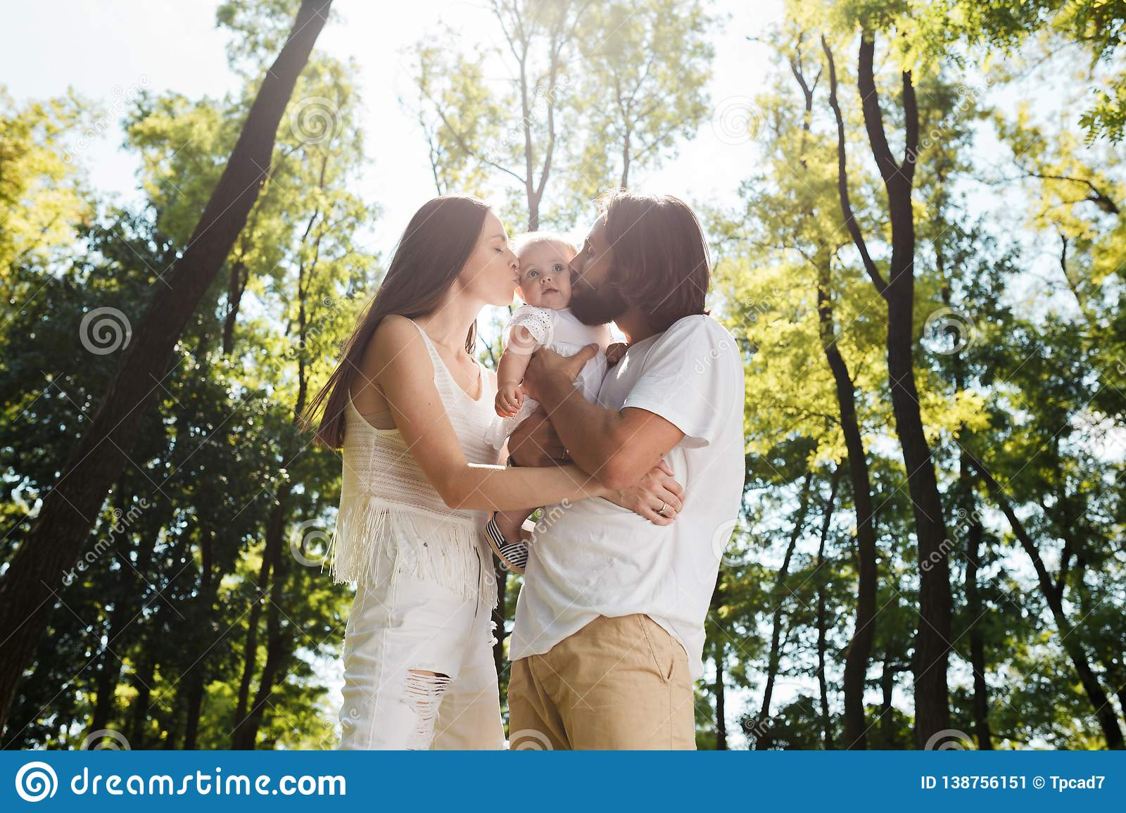 Happy family on the open air. Young dark-haired woman and her husband are kissing their charming little daughter.
