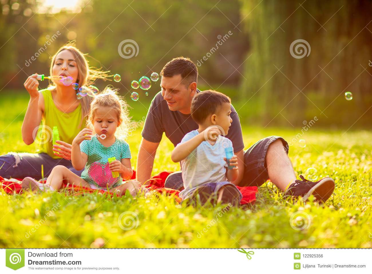 Happy Family In The Park- Family With Children Blow Soap