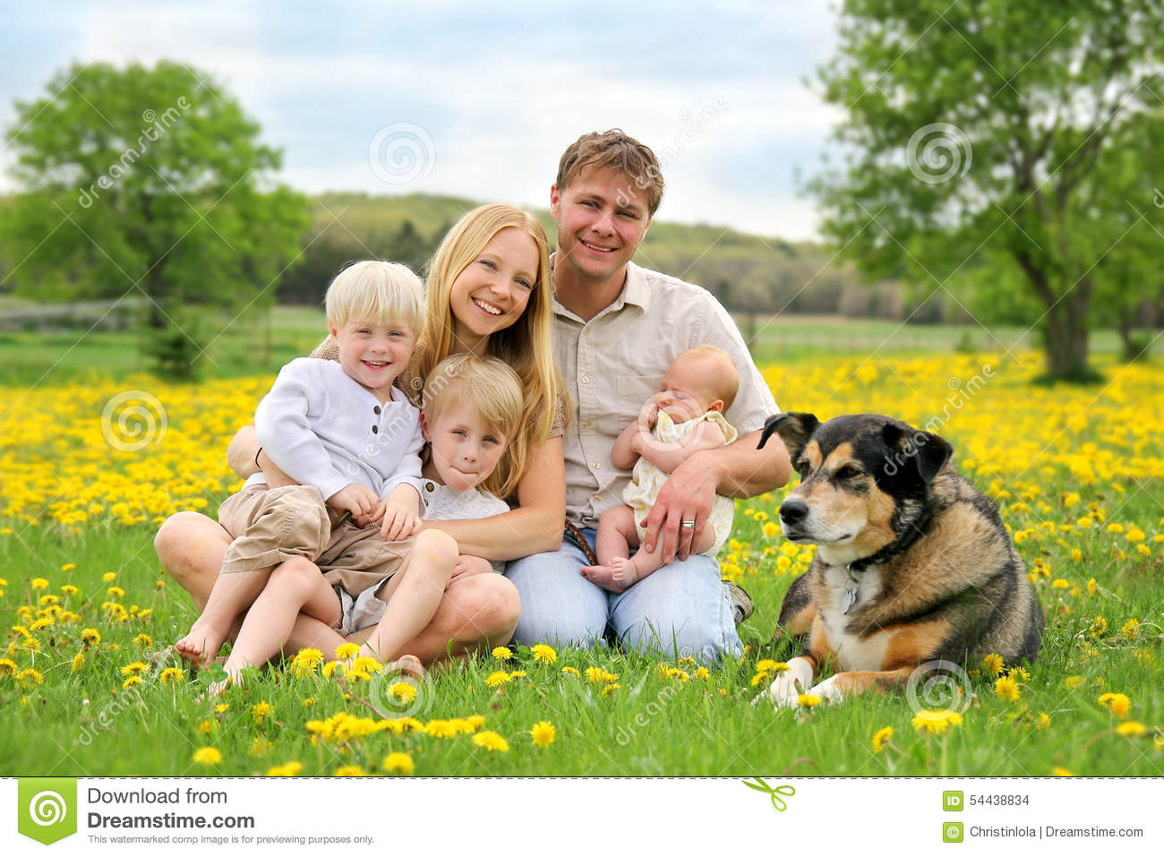 Happy Family And Pet Dog In Flower Meadow