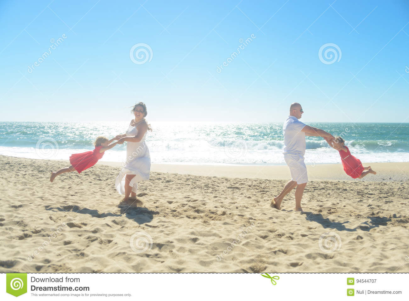 6854638f1f Mom and Dad in white clothes spinning around two daughters in red dresses  on the beach on sunny day.