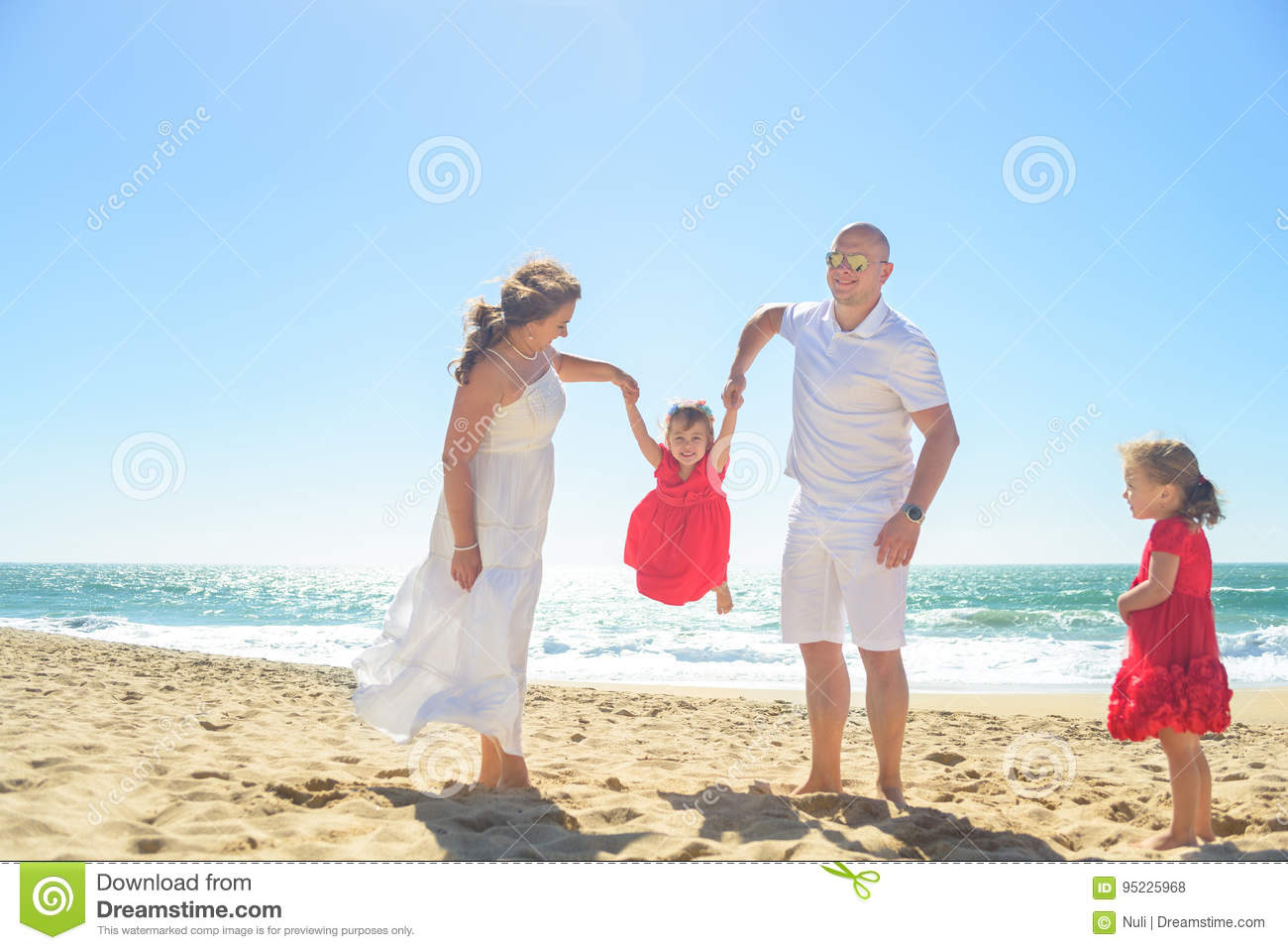 7dd4a2068b Mom and Dad in white clothes playing with two daughters in red dresses on  the beach on sunny day.