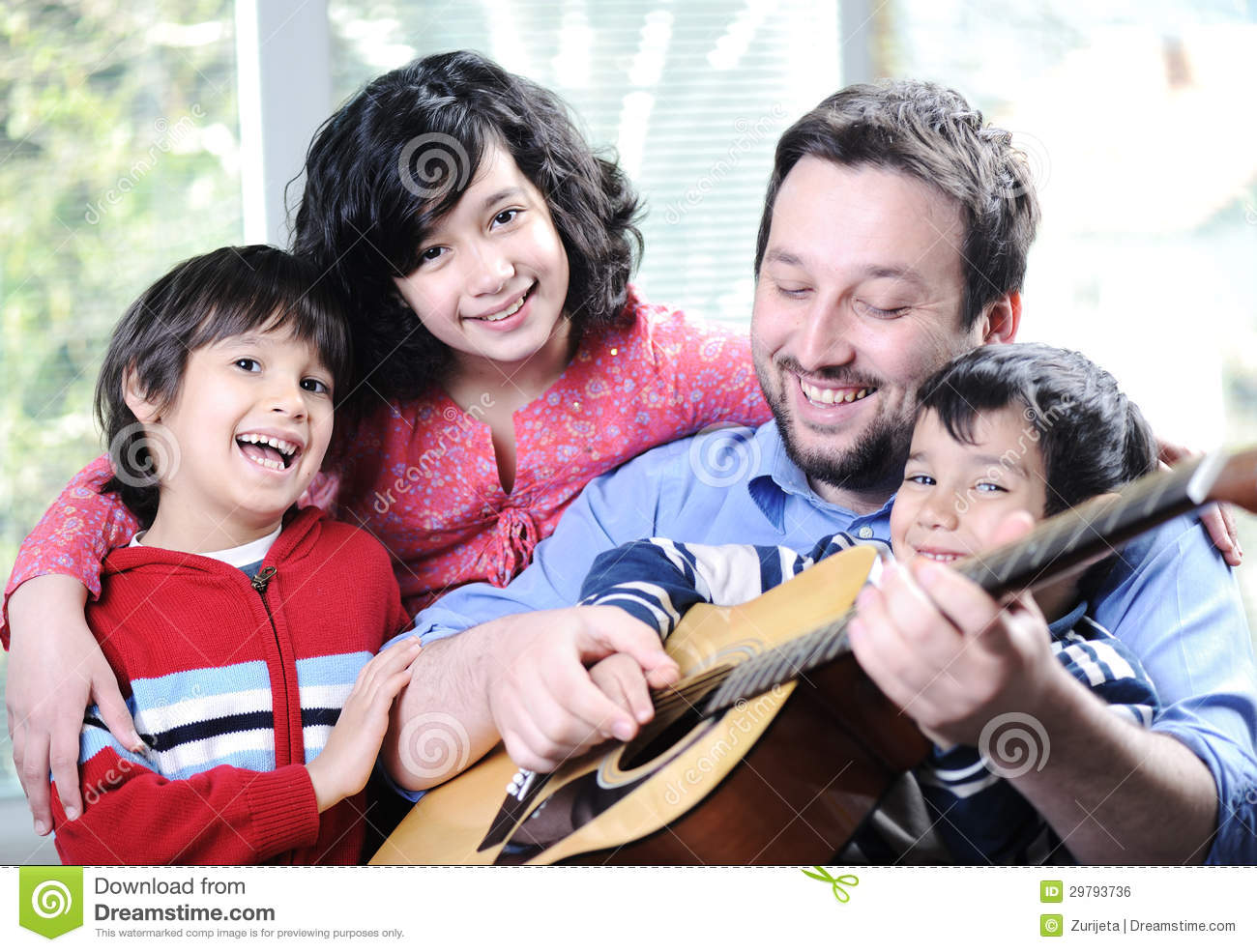 Happy family playing guitar together