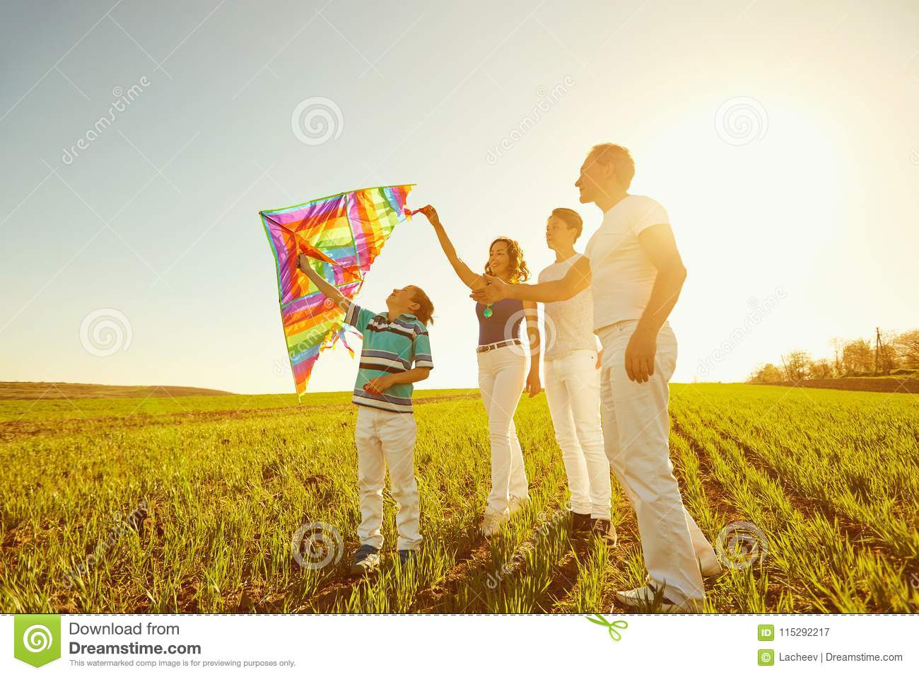 Happy family playing with a kite on nature in spring, summer.