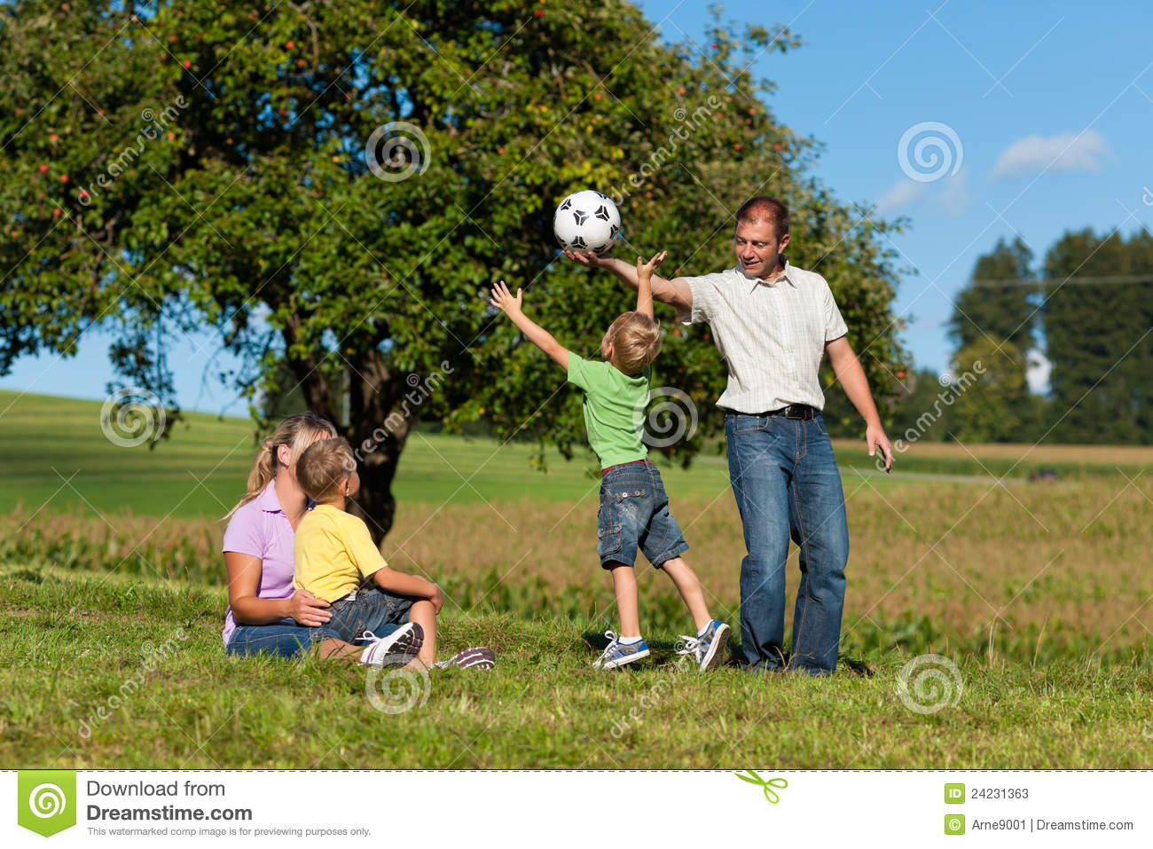 Happy family is playing soccer in summer