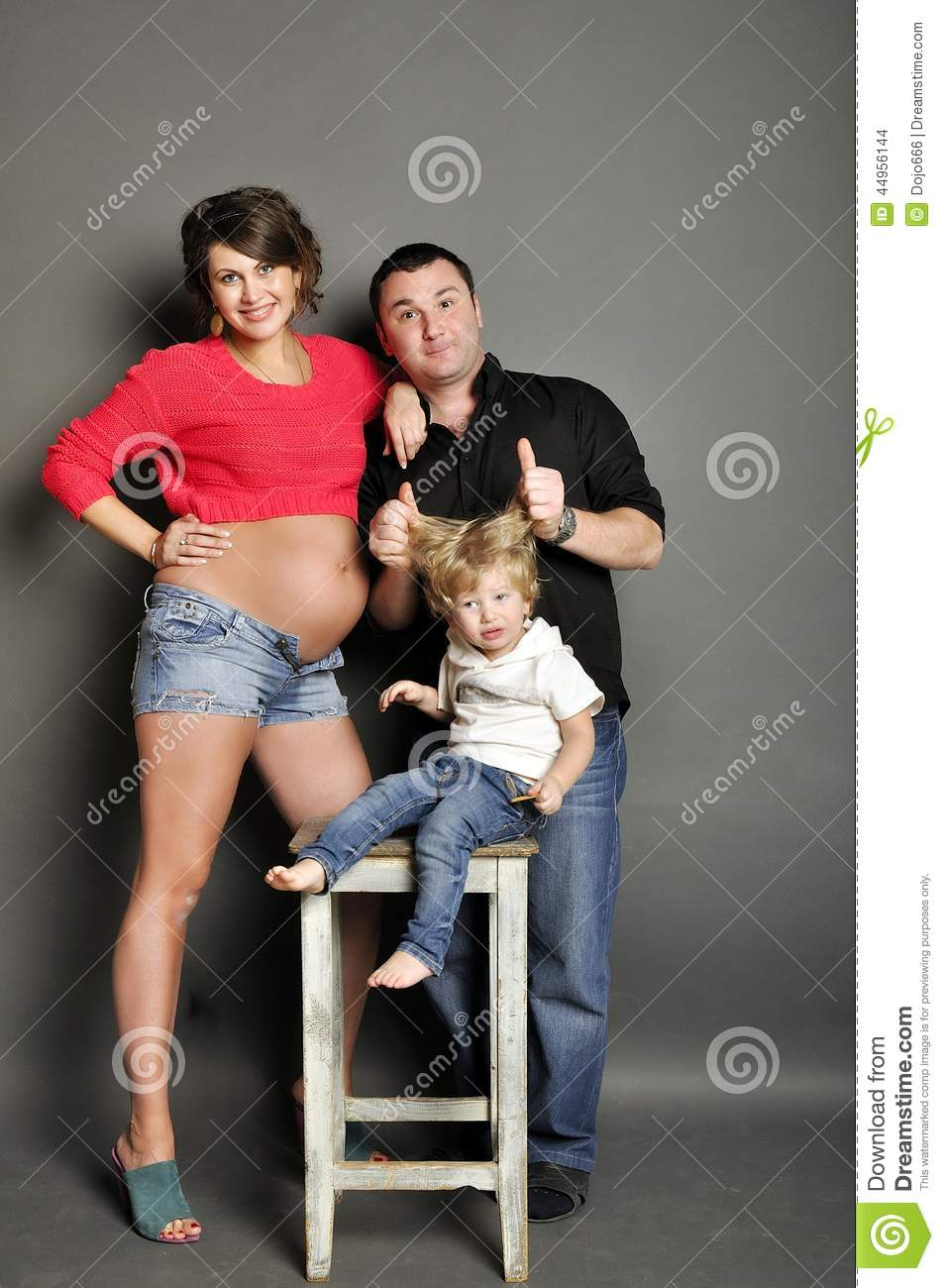 Happy Family With Pregnant Woman On Gray Background Stock Photo