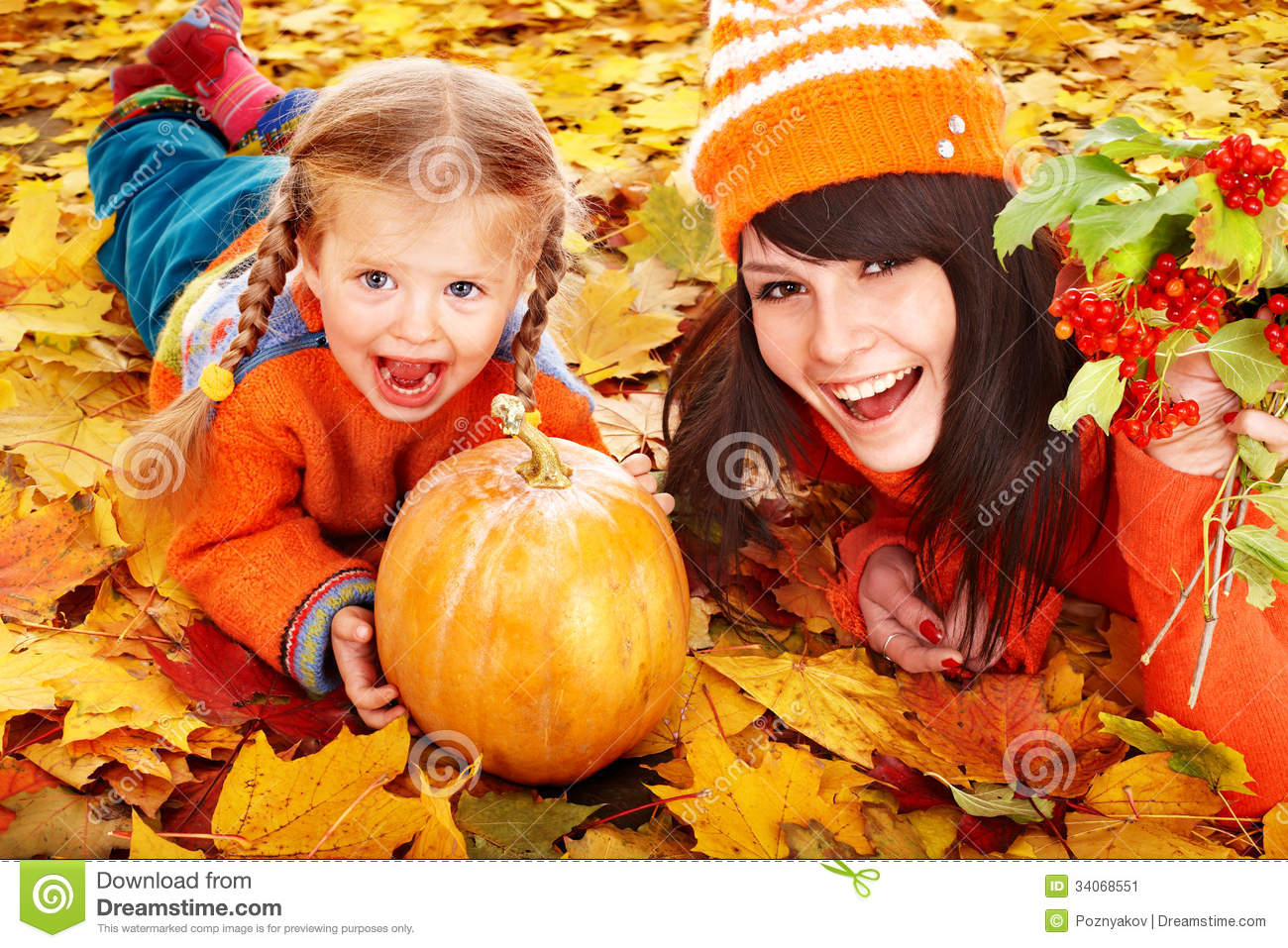 Happy family with pumpkin on autumn leaves.