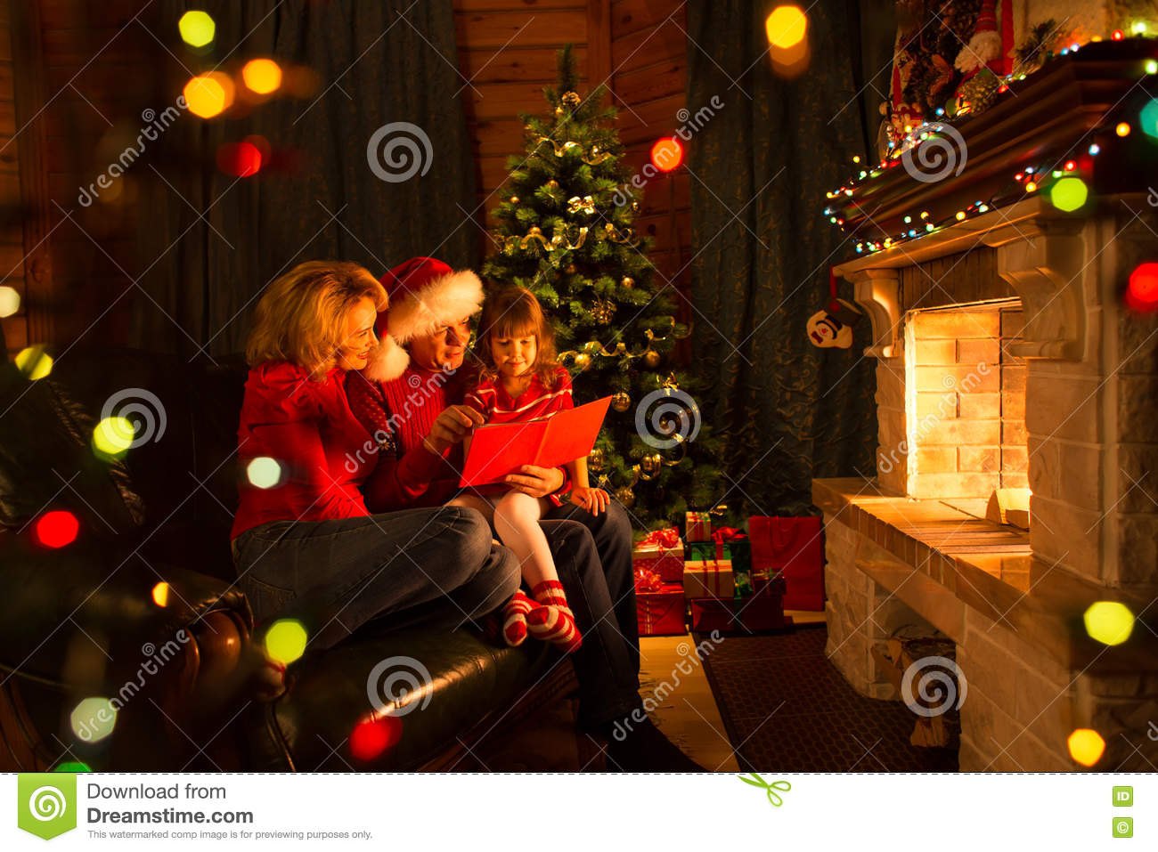 Happy family reading book at home by fireplace in warm and cozy ...