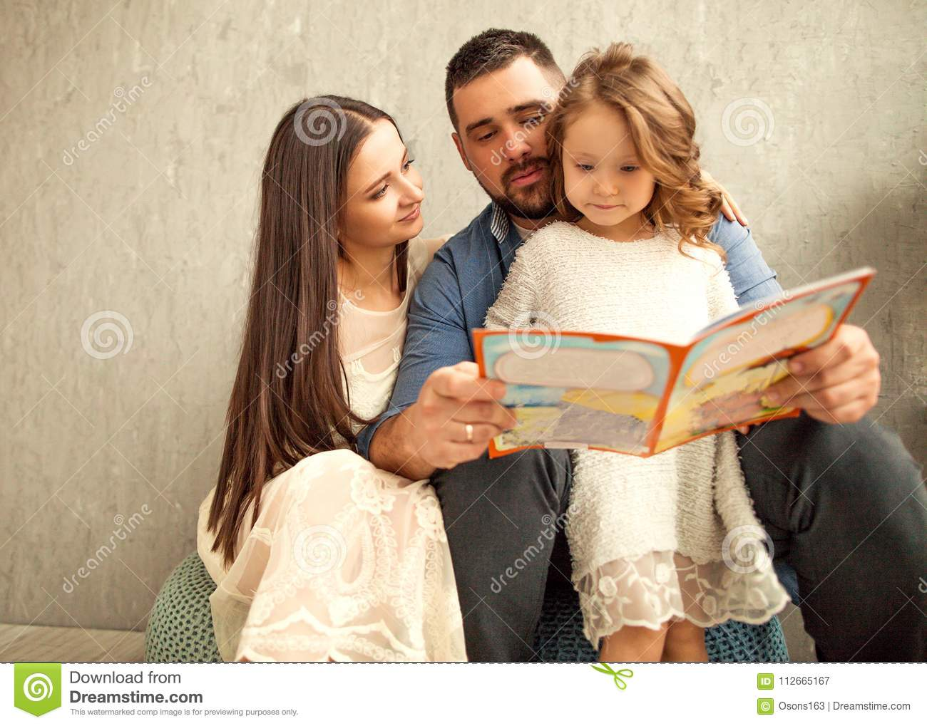 Happy family reading a book to her daughter. Mothers Day.