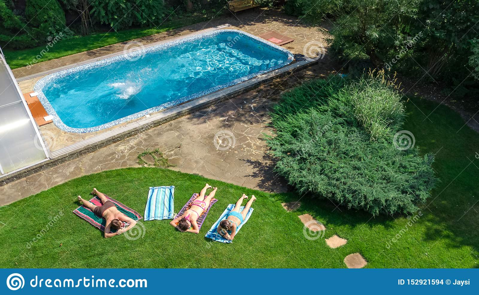 Happy family relaxing by swimming pool, aerial drone view from above of parents and kids have fun on vacation, family weekend
