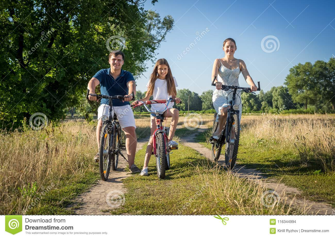 Happy young family riding bicycles with child in field