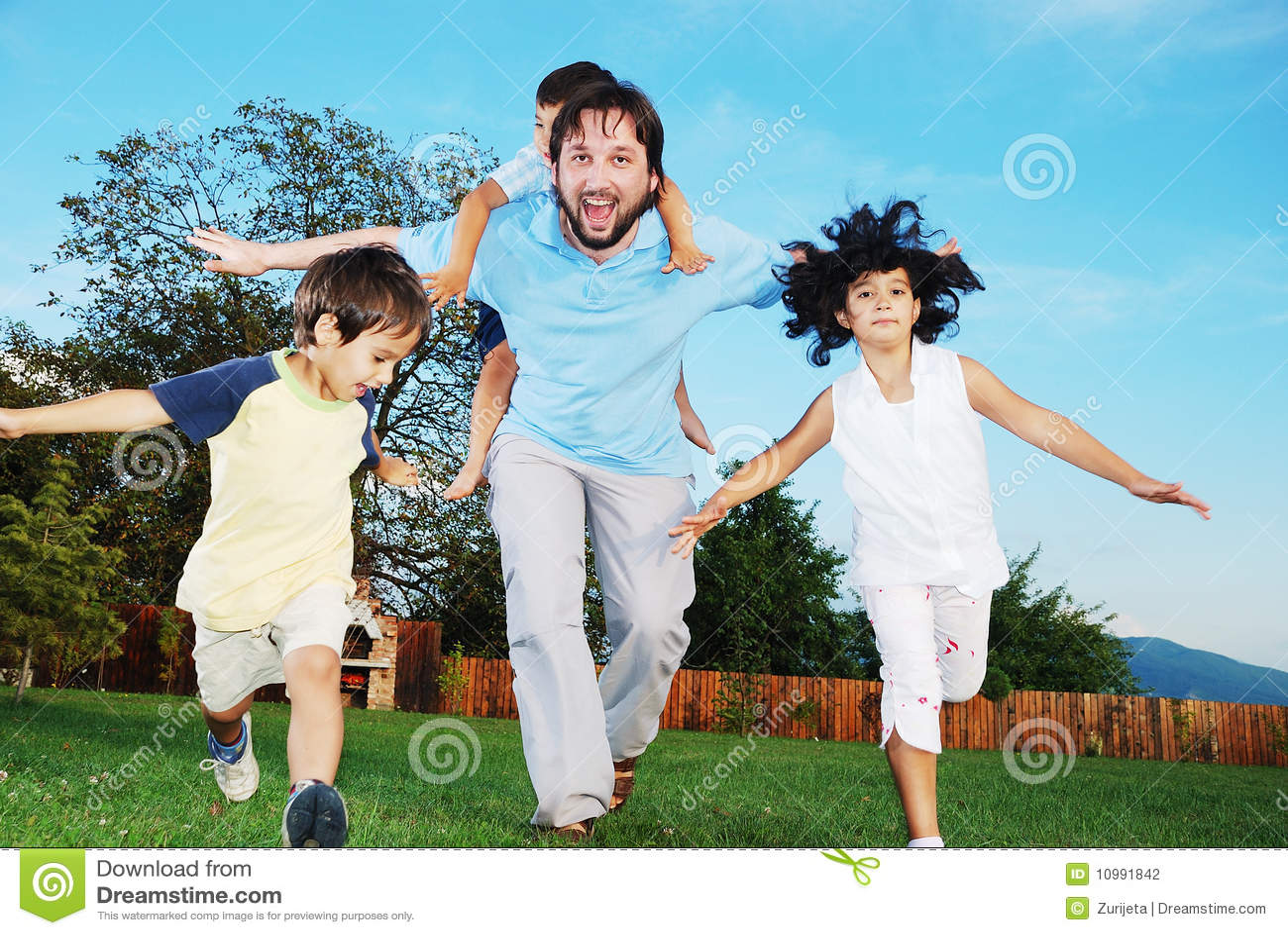 Happy family running outdoor, on beautiful garden