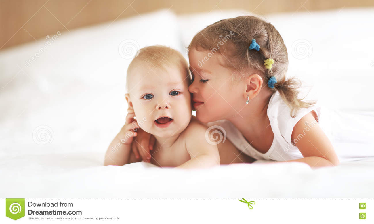 Happy Family Sister Kisses Baby Brother Stock Photo
