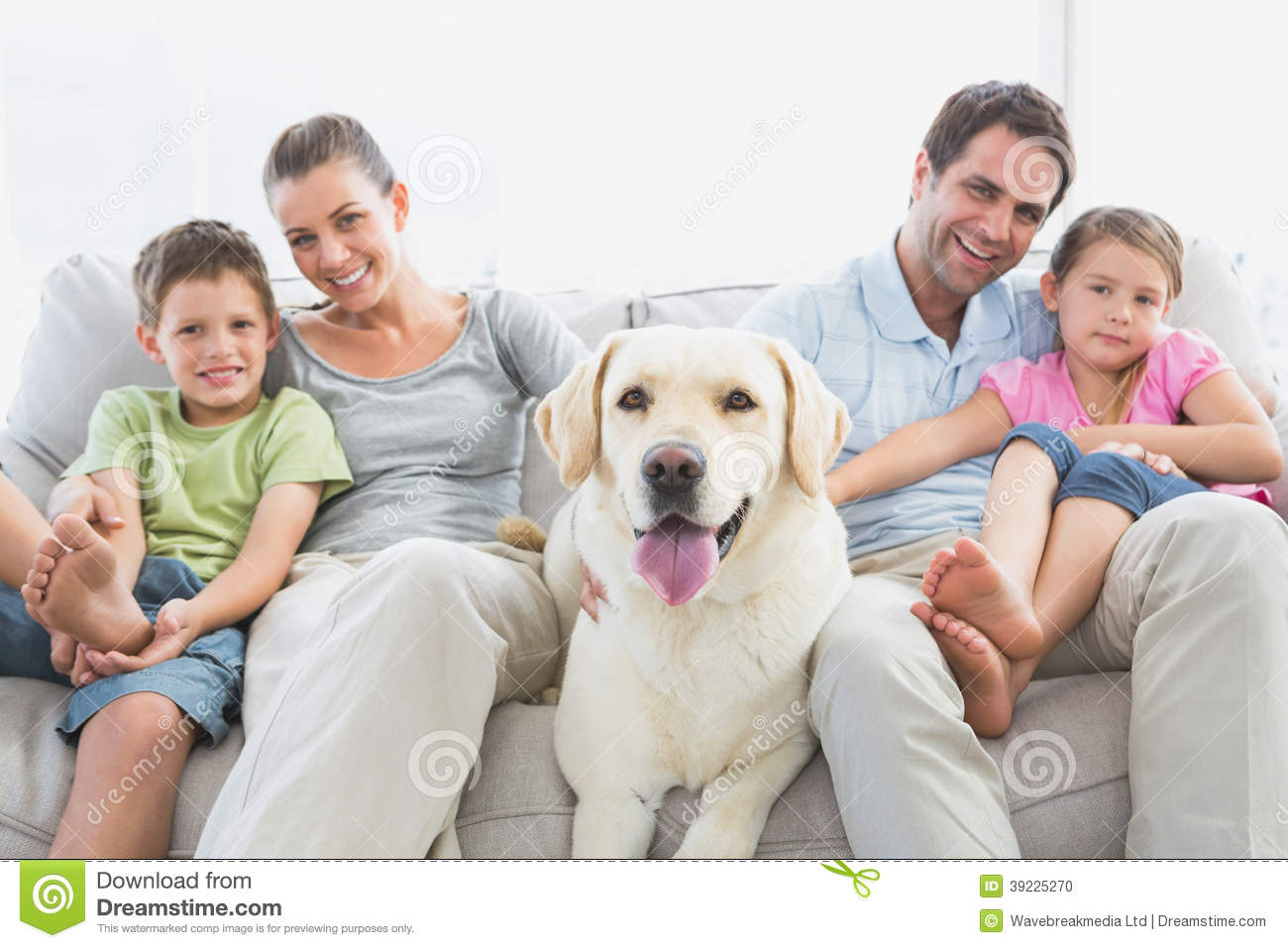sitting on couch with their pet labrador at home in the living room