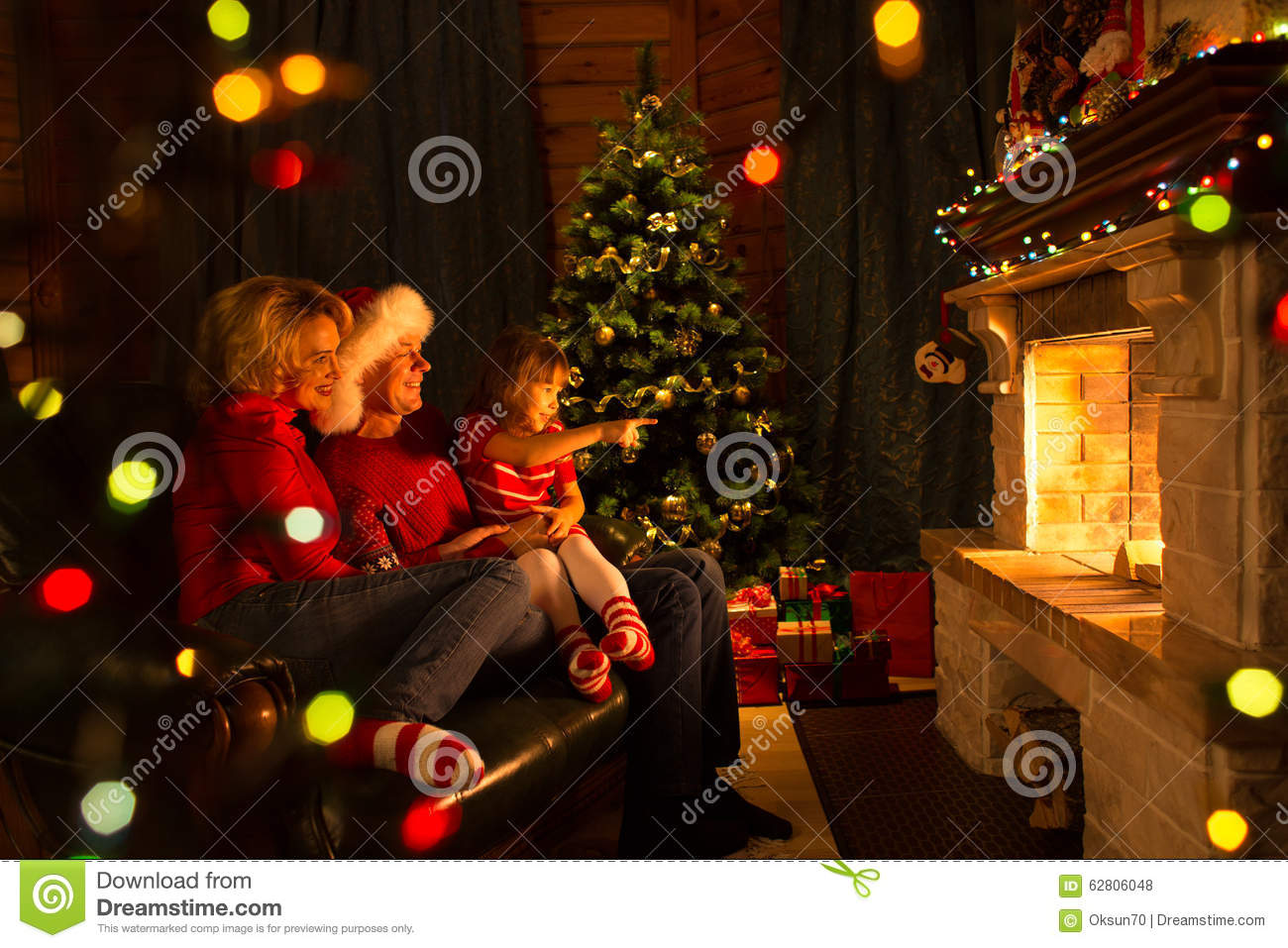Happy Family Sitting By Fire Place At Christmas Stock Photo