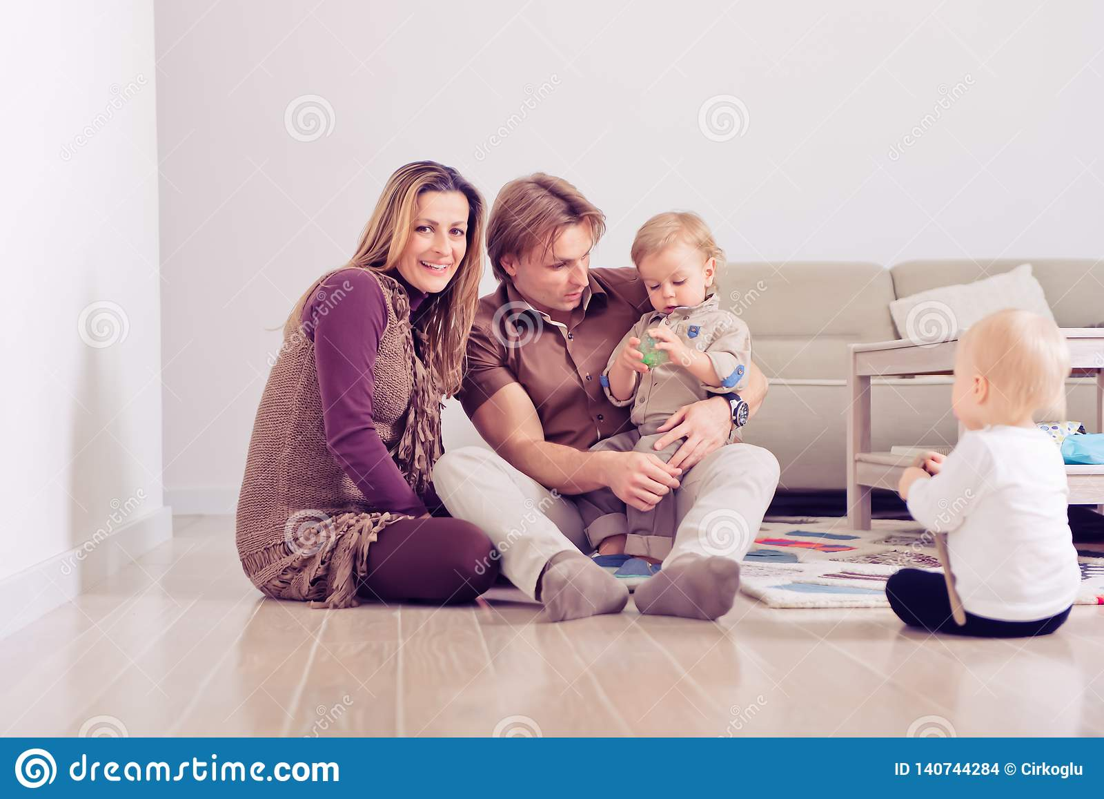 Happy family sitting on floor with their little babies family spending time at home with their
