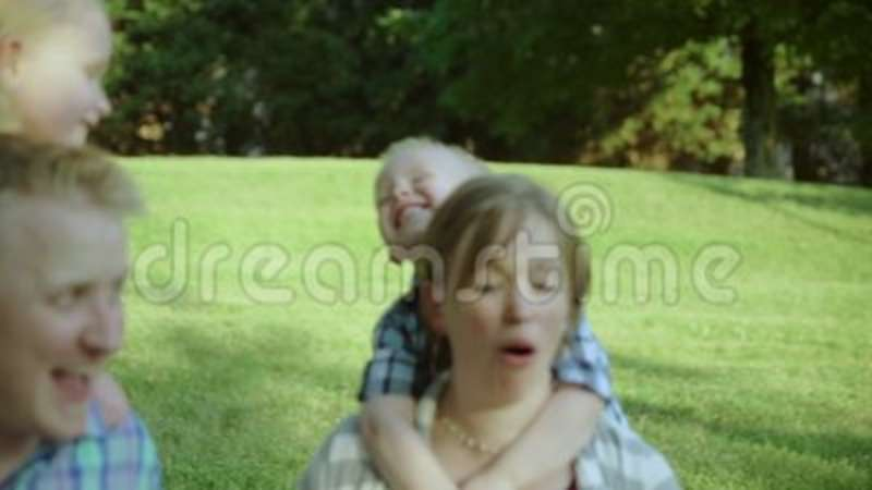 Happy Family Sitting On A Grass During Summer Rest In Park Slow