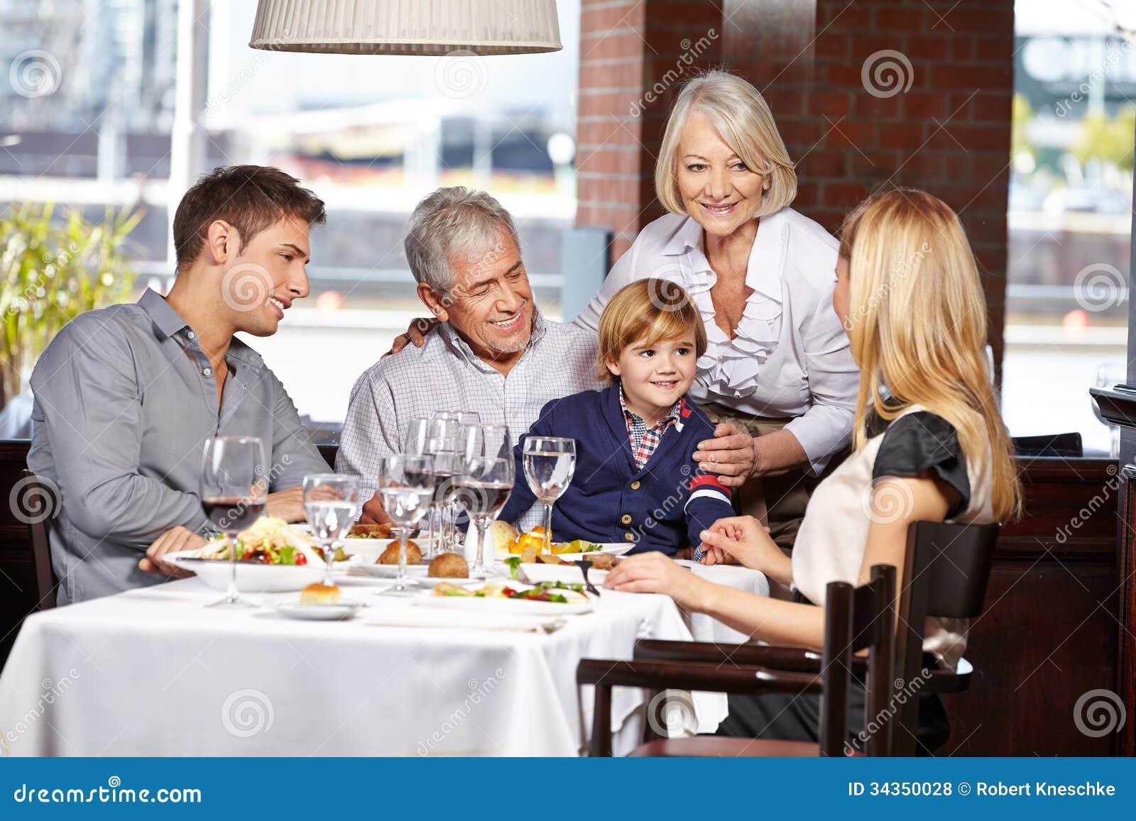 Happy Family Sitting In Restaurant