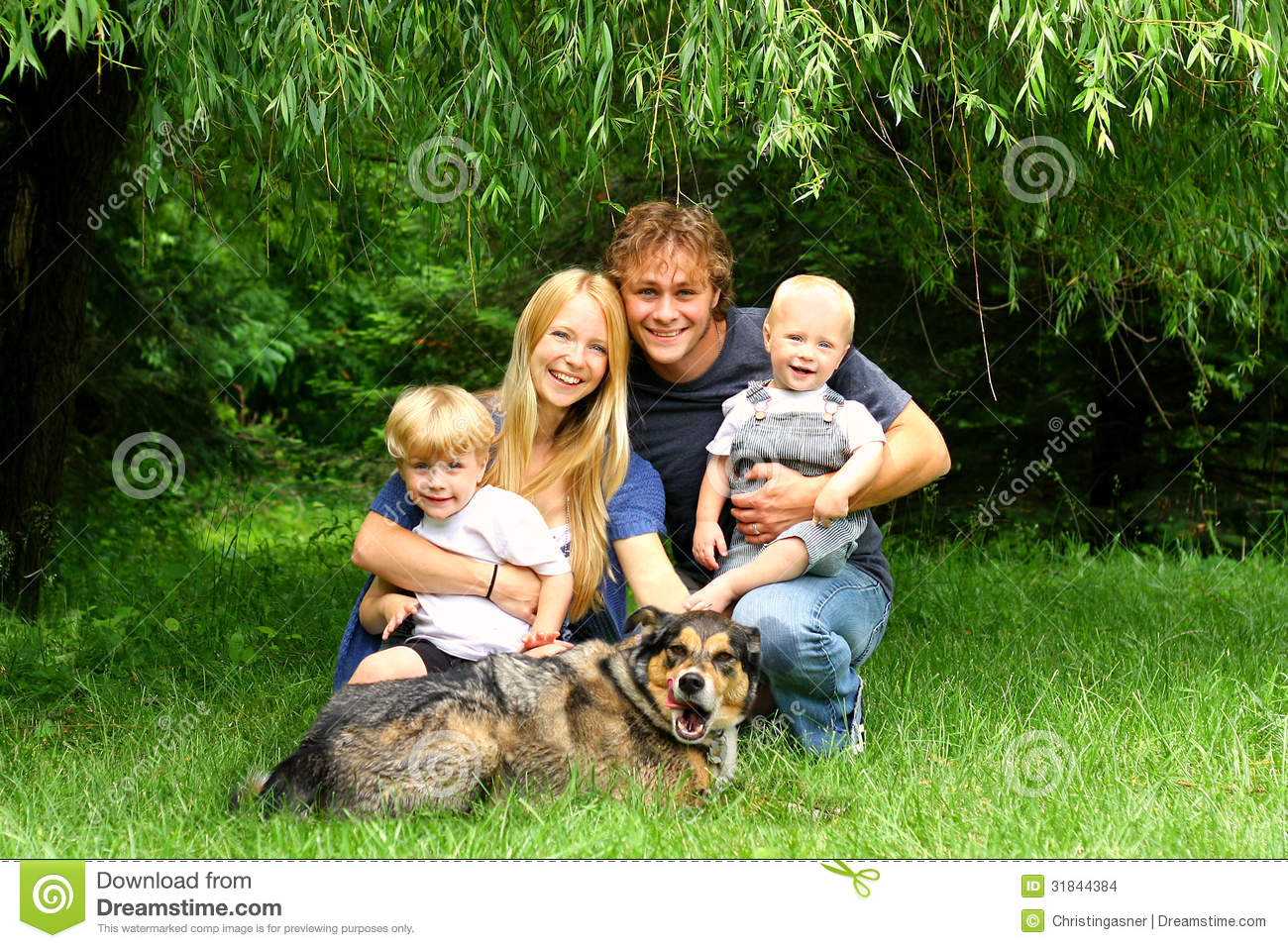Happy Family Sitting Under Willow Tree Stock Images