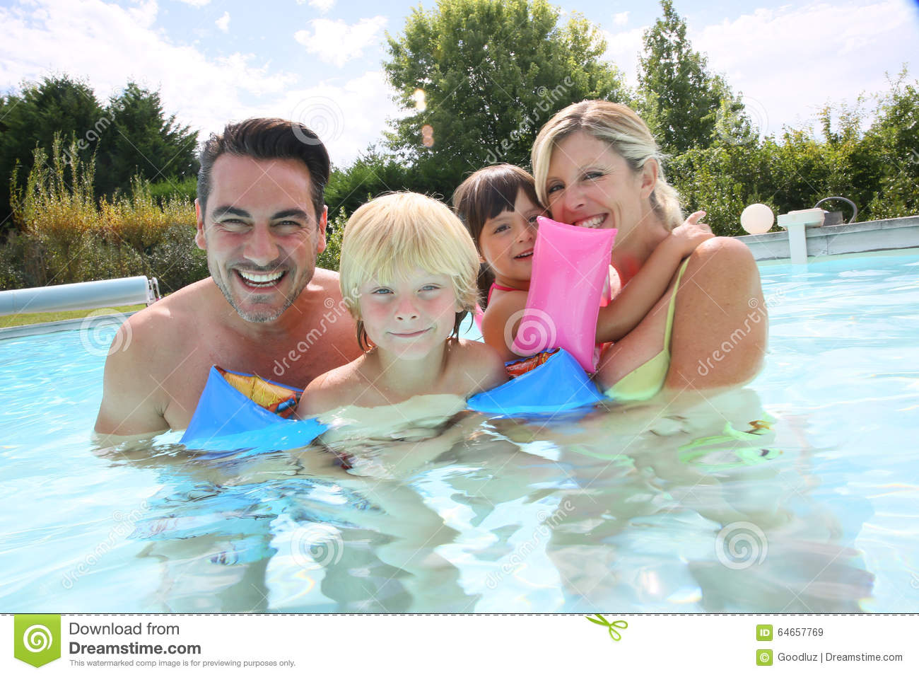 Happy family spending good time in swimming pool