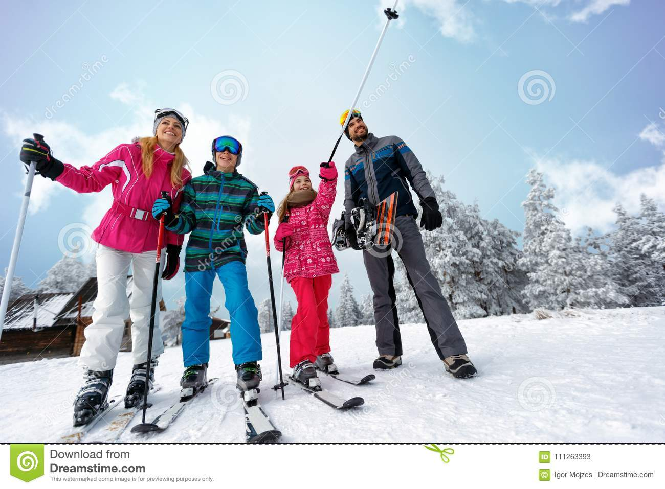 Family sport skiing and snowboarding time on sunny day
