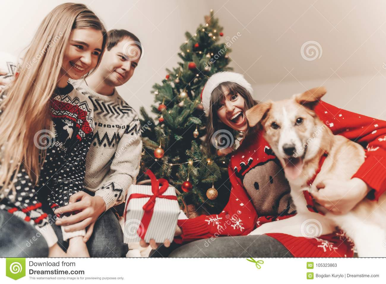 Download Happy Family In Stylish Sweaters And Cute Funny Dog Exchanging G Stock Image
