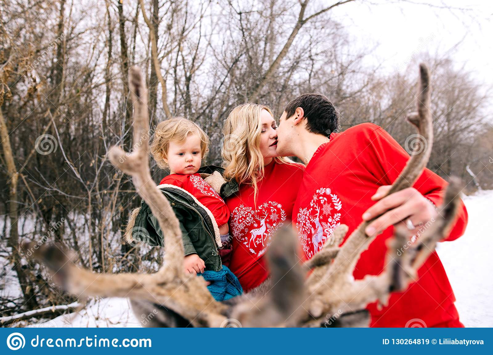 Happy family at sunset. Father, mother and child daughters are having fun and playing on snowy winter walk in nature, kiss. Frost
