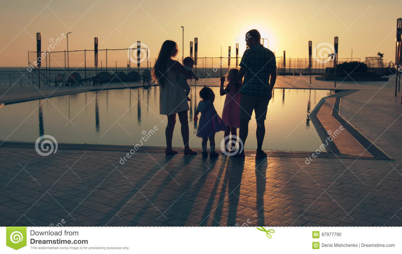 Happy Family With Three Children Admiring The Sunset