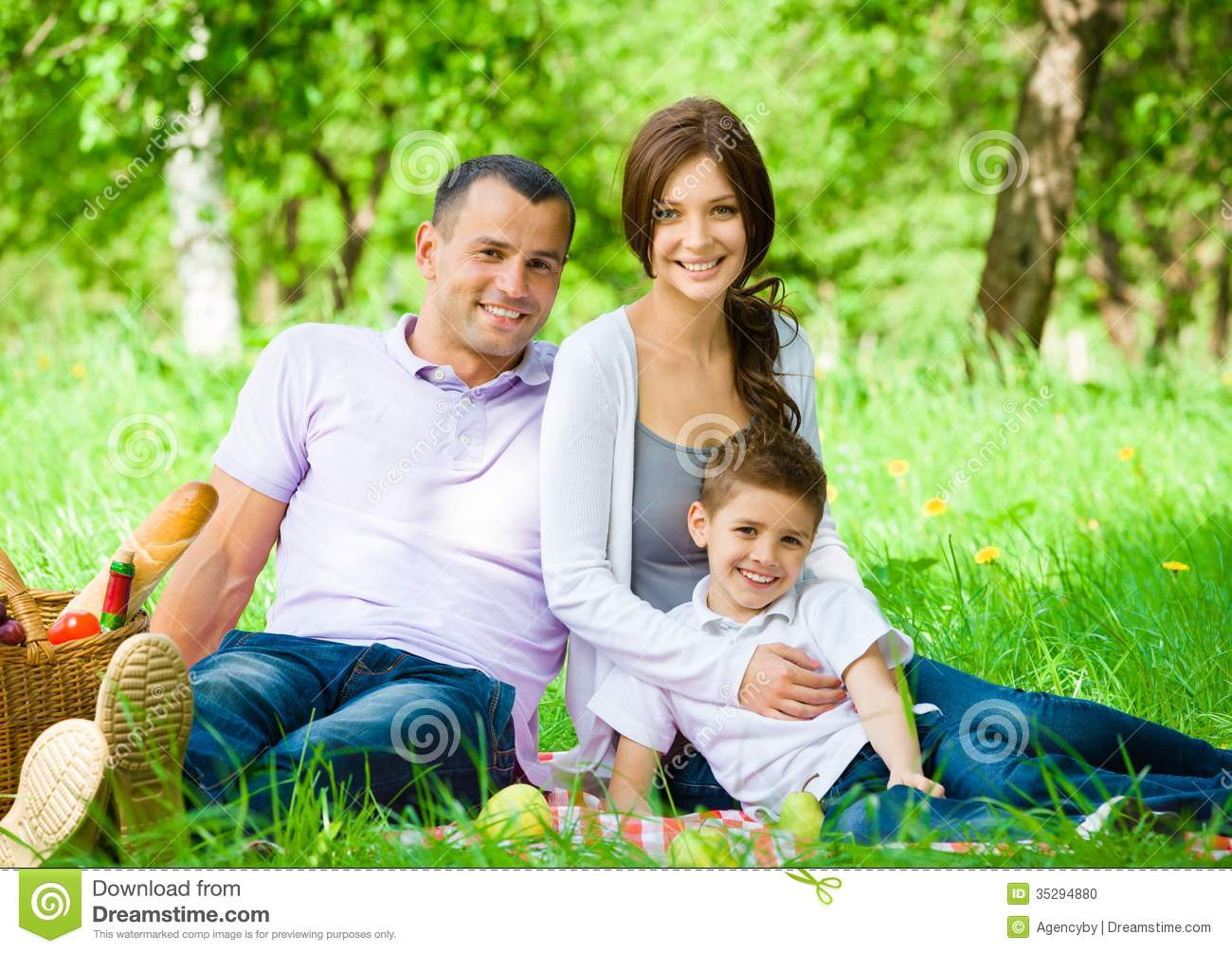 Happy family of three has picnic in green park