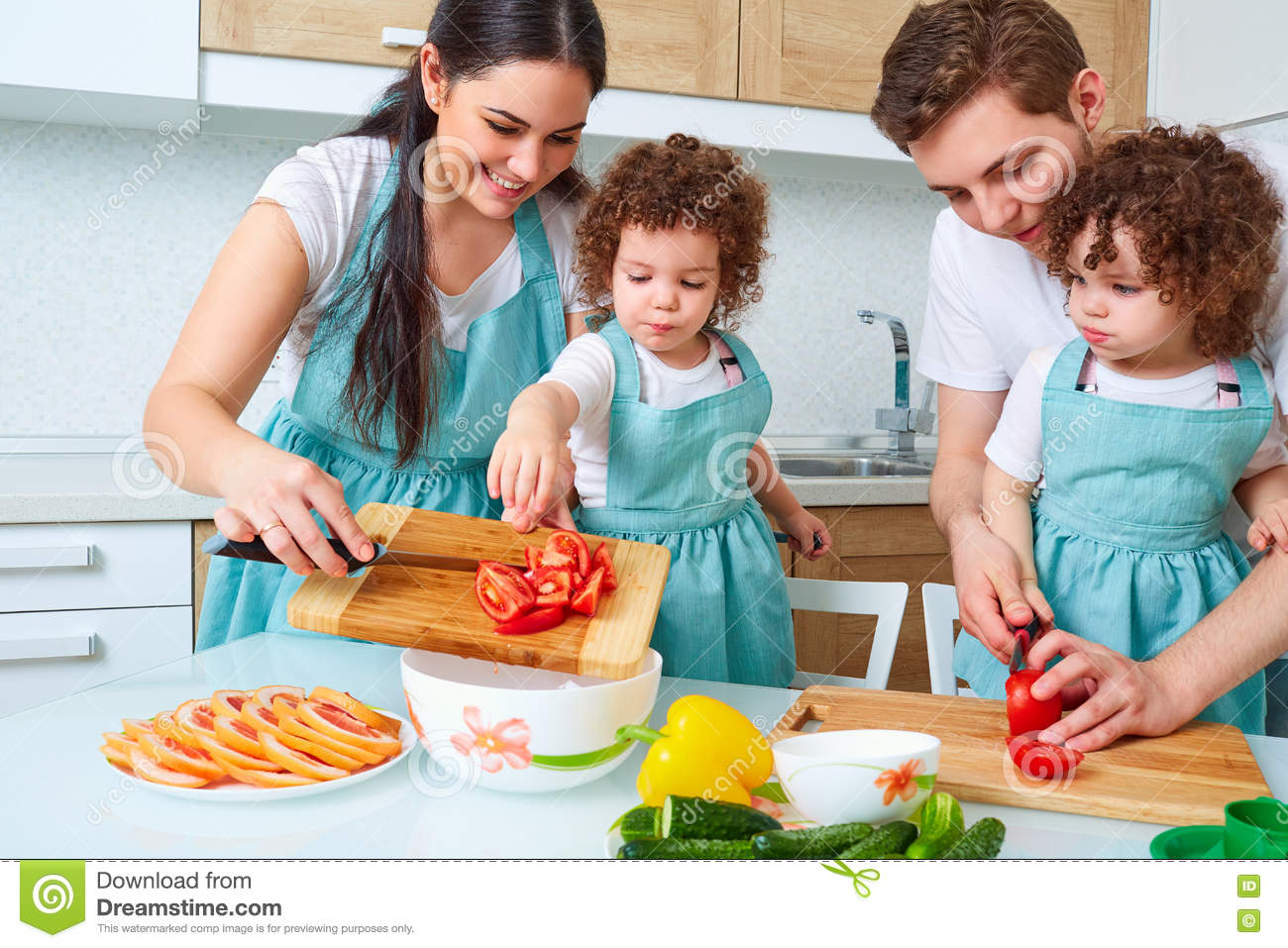 Happy Family With Twin Daughters In The Kitchen. Cheerful Mother ...