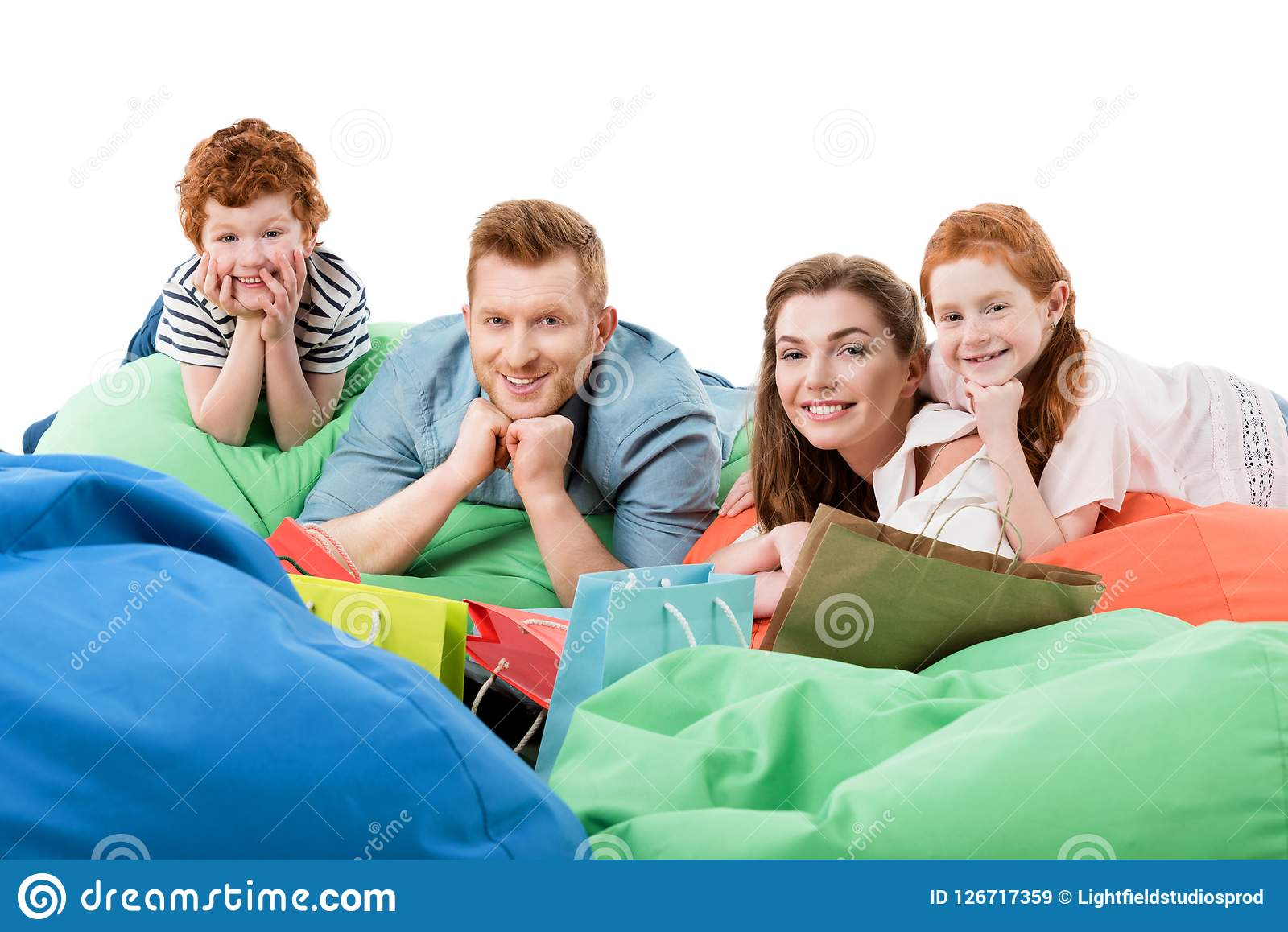 happy family with two children resting on bean bag chairs and smiling at camera after shopping