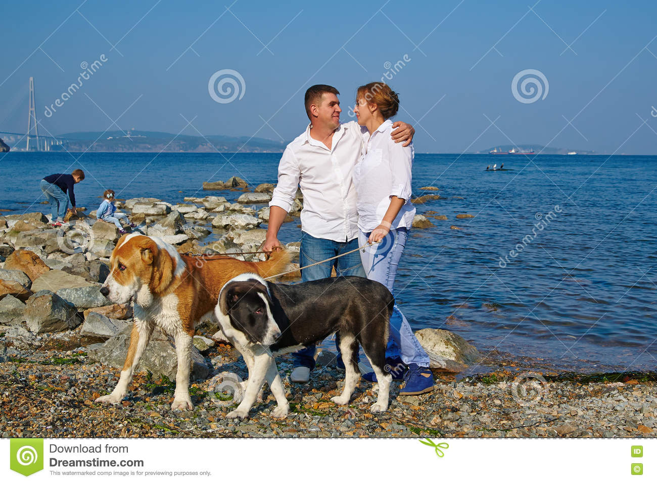 Happy family with two children, two large dogs for a walk at the seaside