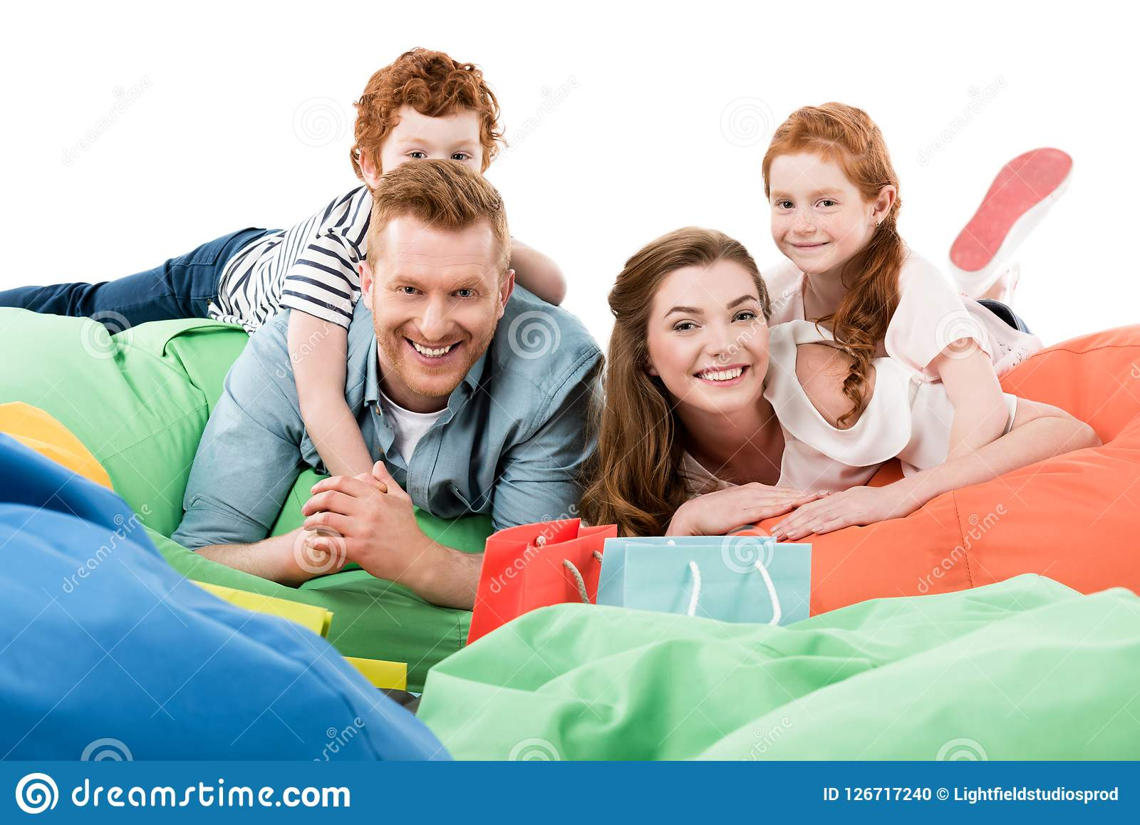 happy family with two kids lying on bean bag chairs and smiling at camera after shopping