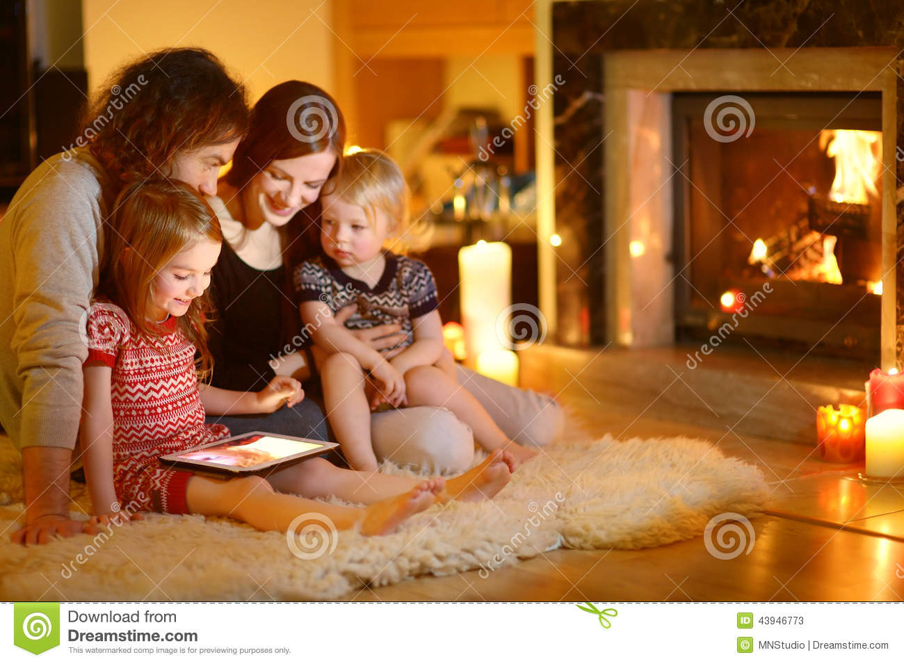 happy family using a tablet pc by a fireplace stock image. Black Bedroom Furniture Sets. Home Design Ideas