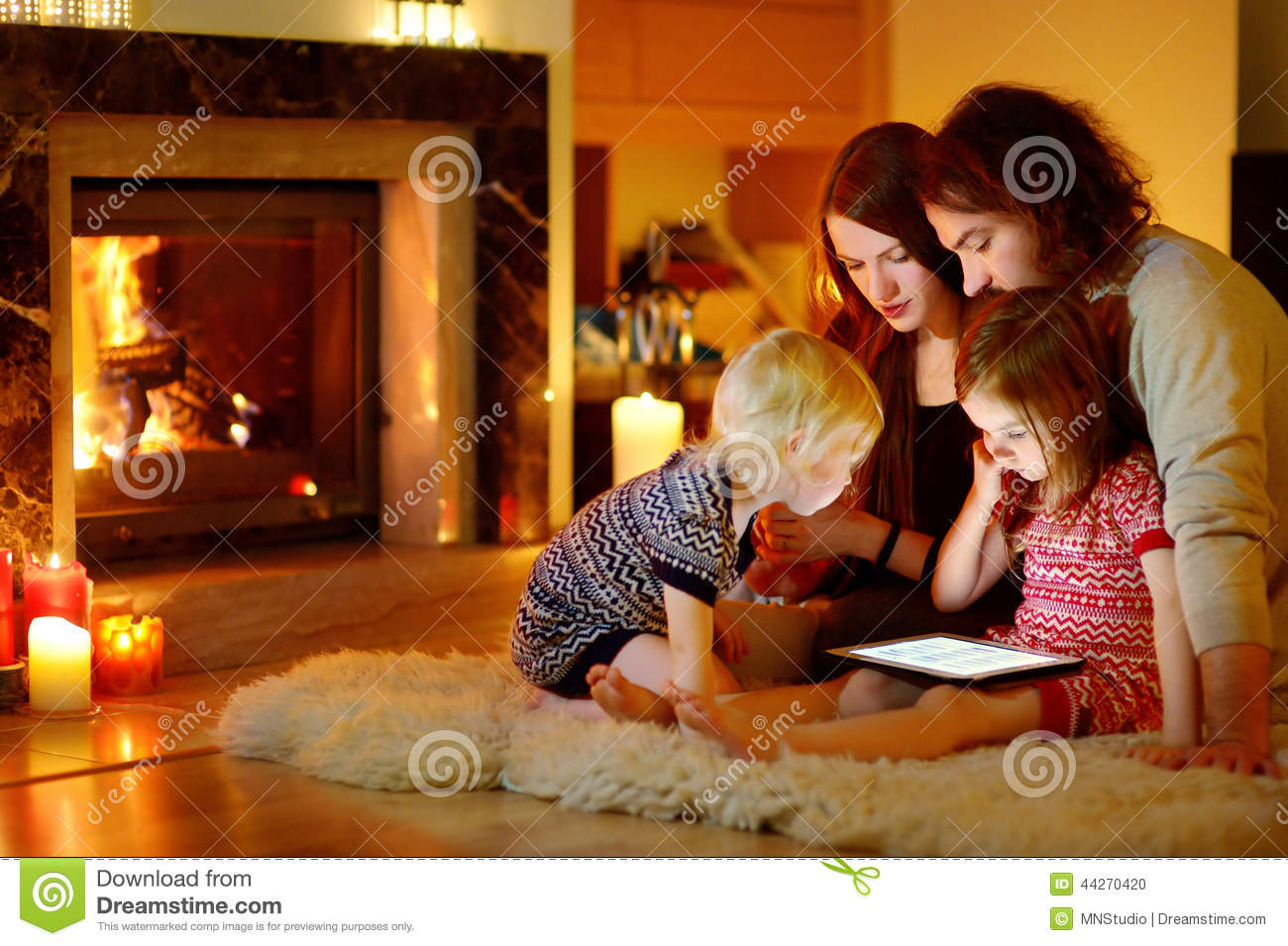 Happy family using a tablet pc by a fireplace stock photo for Living room ideas young family