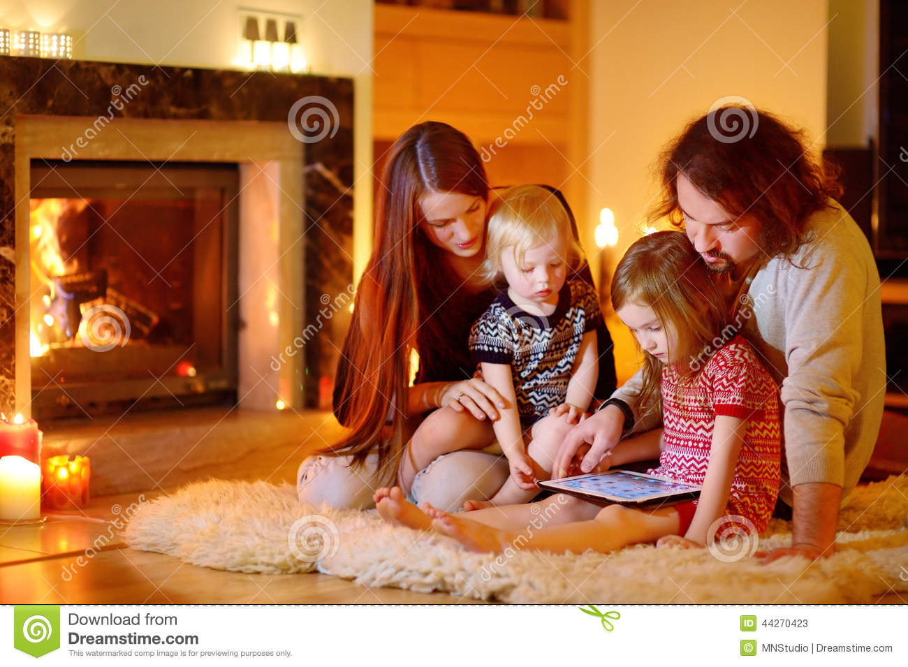 Happy Family Using A Tablet Pc By A Fireplace Stock Photo - Image ...