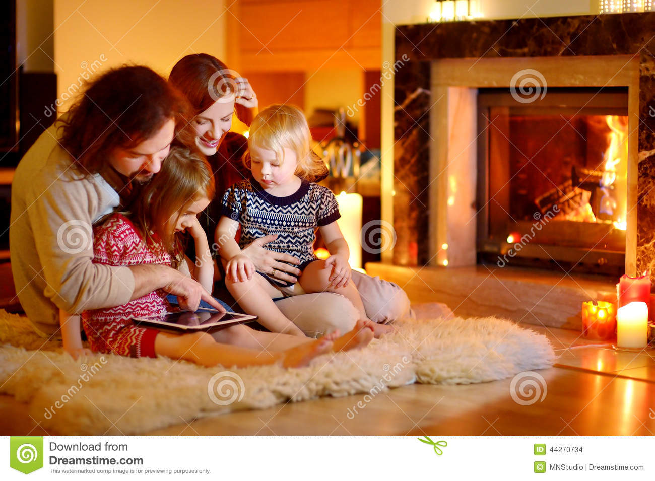 happy family using a tablet pc by a fireplace stock photo image 44270734. Black Bedroom Furniture Sets. Home Design Ideas