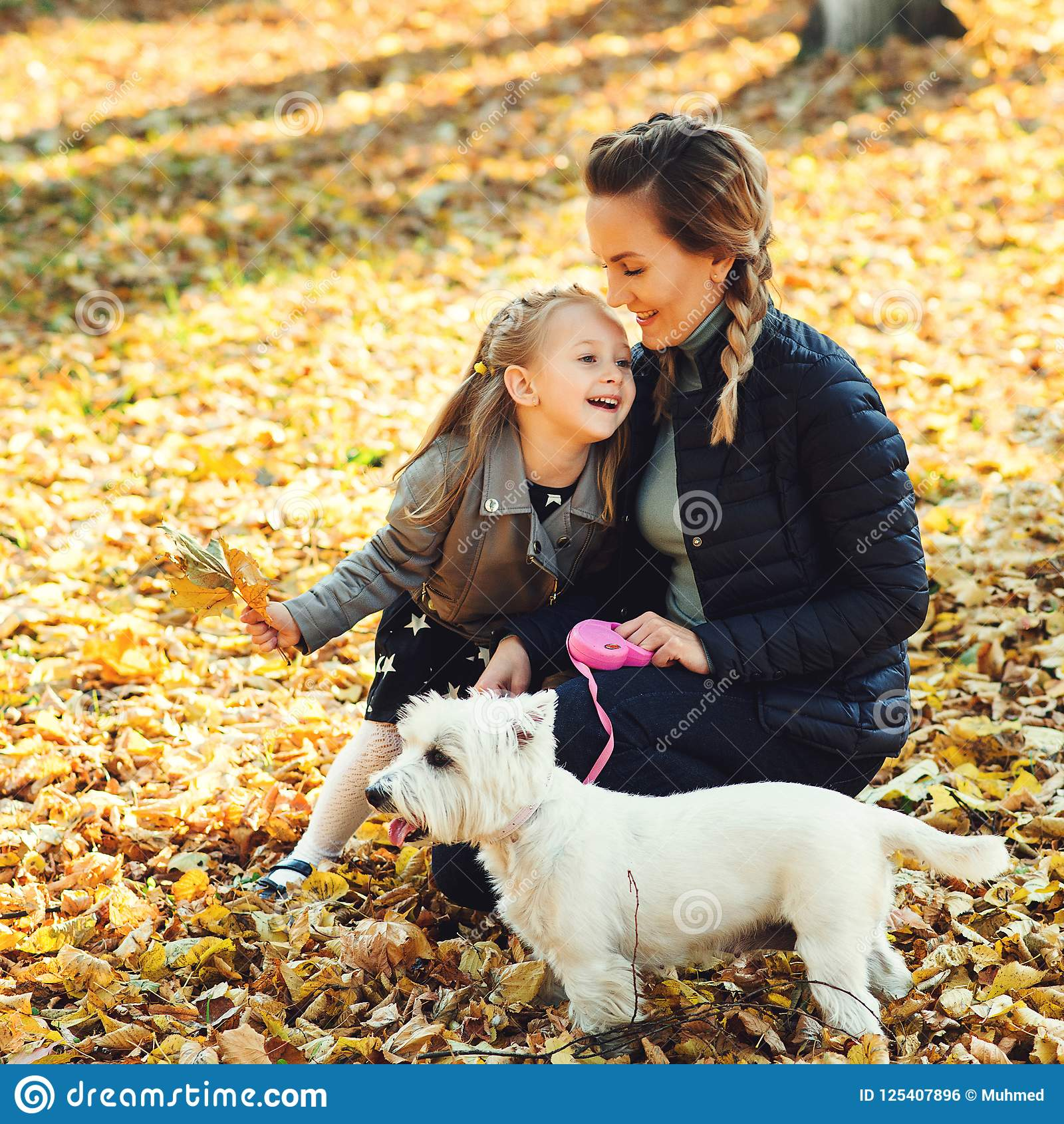 Happy family walking with dog in autumn park. Young mother and daughter with white dog having fun in fallen leaves. Autumn holiday