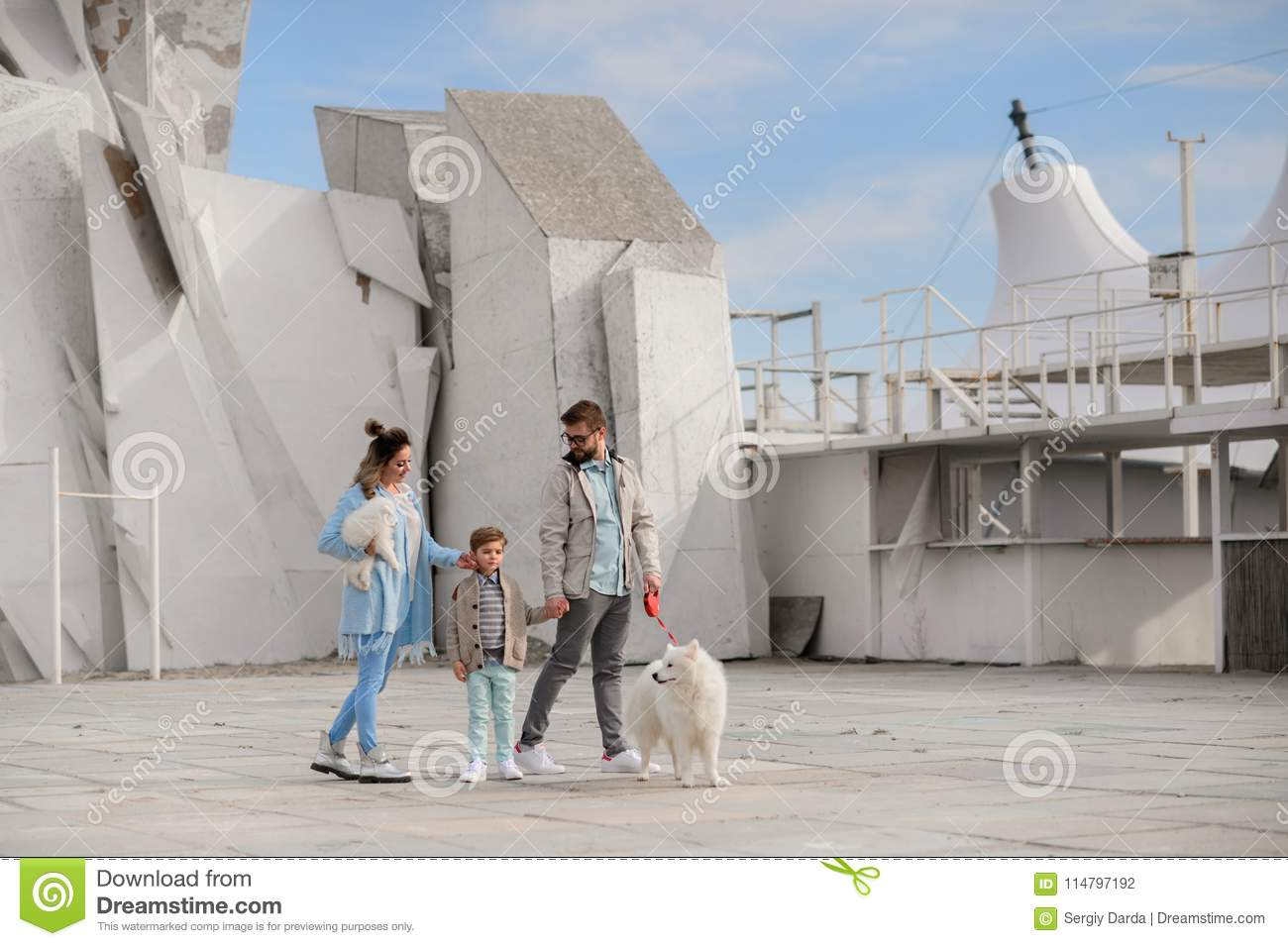 The family walks with a dog.