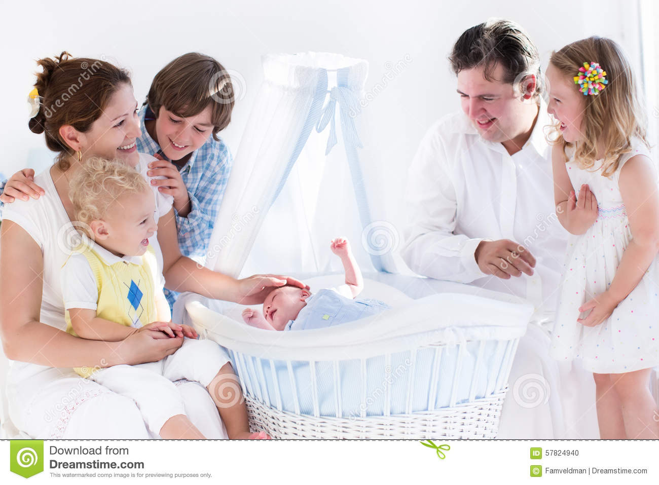 Happy Family Watching New Baby In A White Crib Stock Photo