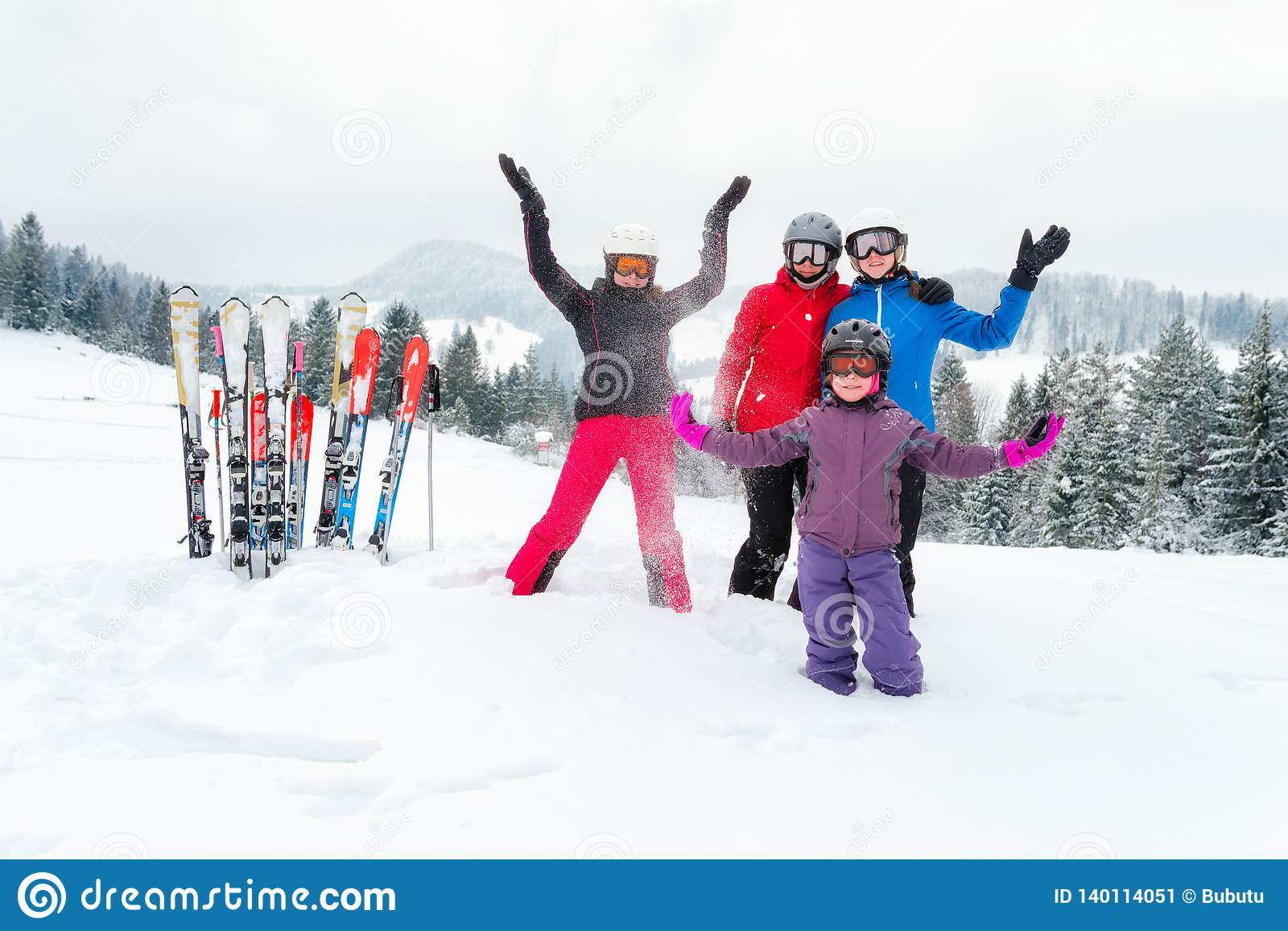 Happy family in winter clothing at ski resort - skiing, winter, snow, fun - mom and daughters enjoying winter vacations