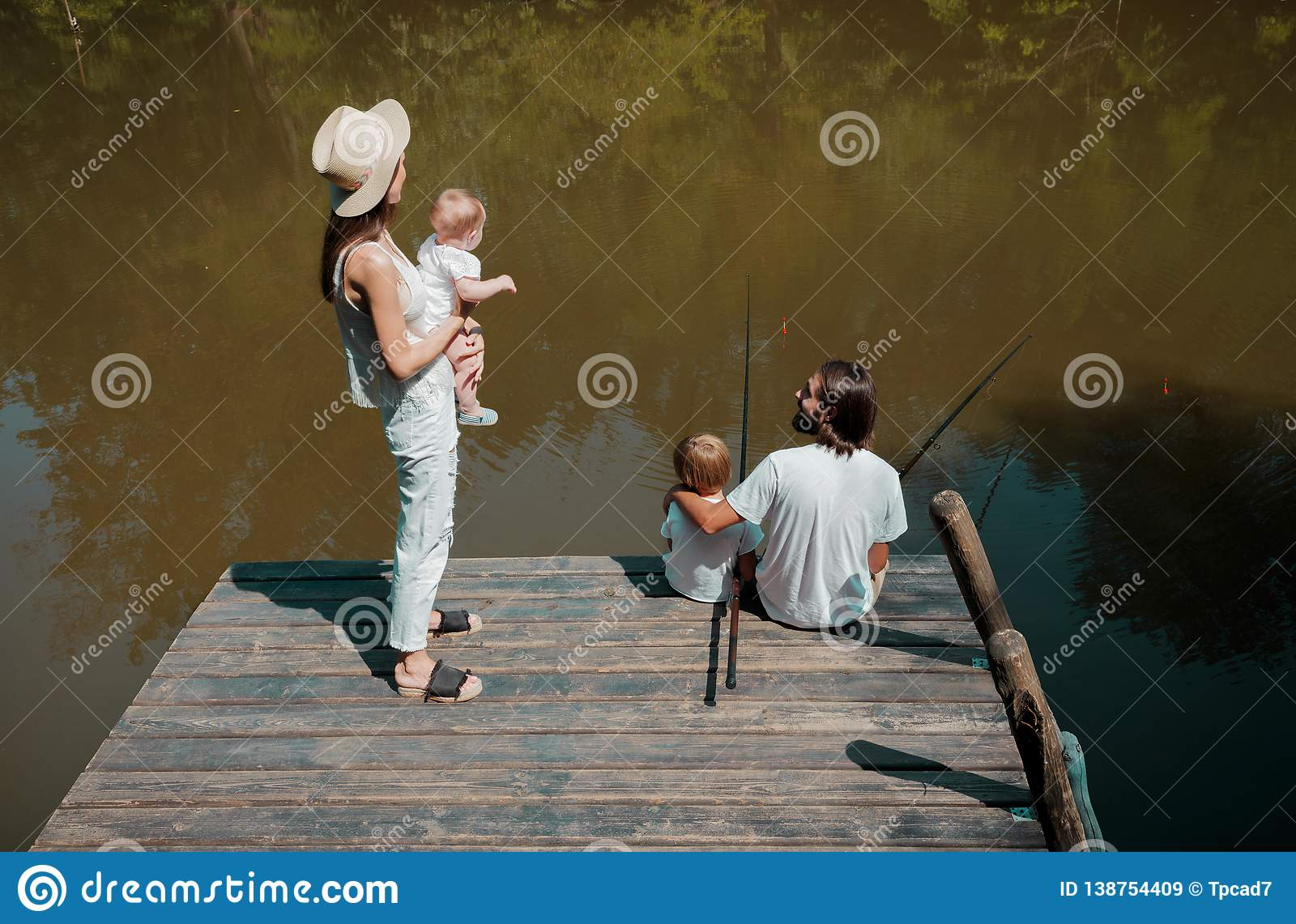Happy family on the wooden pier. Mother is holding in the arms l