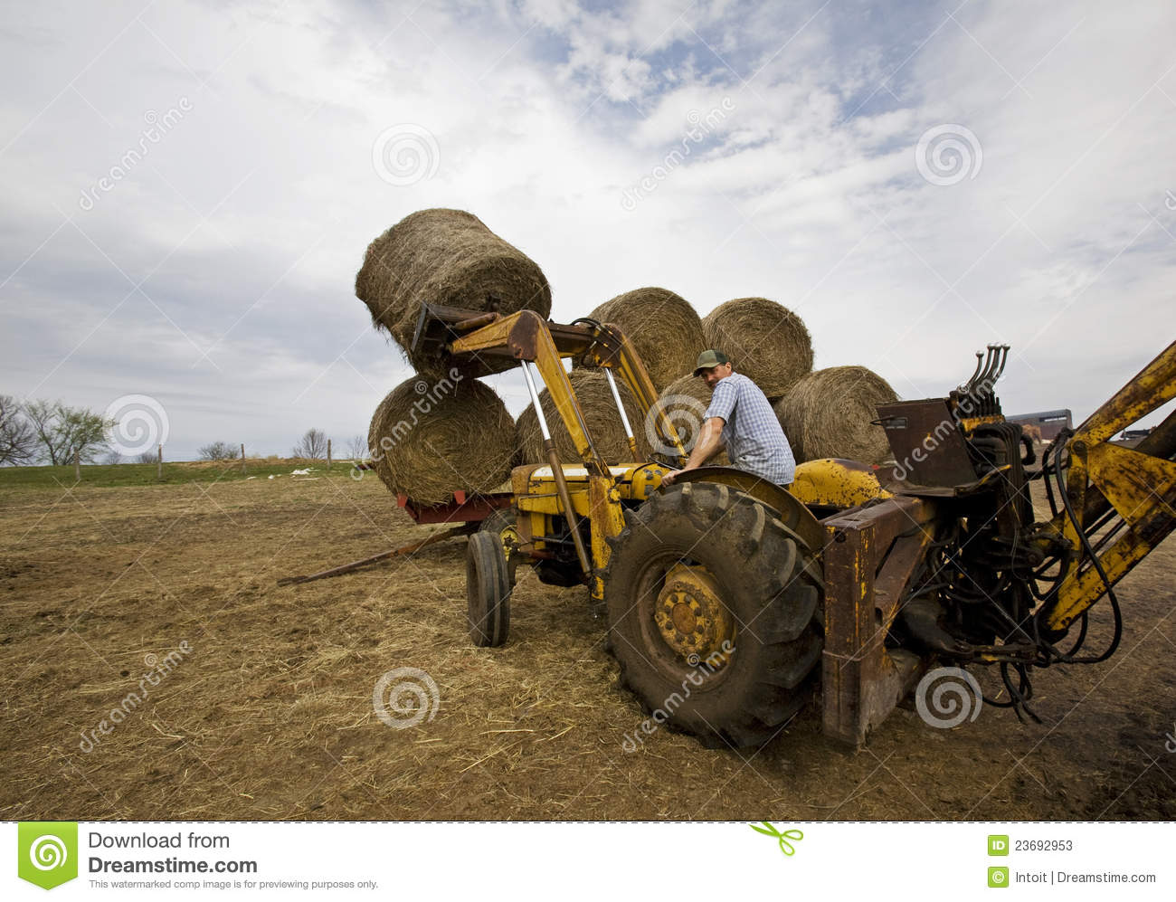 Hay Farmer Tractor Cartoon : Happy farmer on tractor with round hay bales stock photos