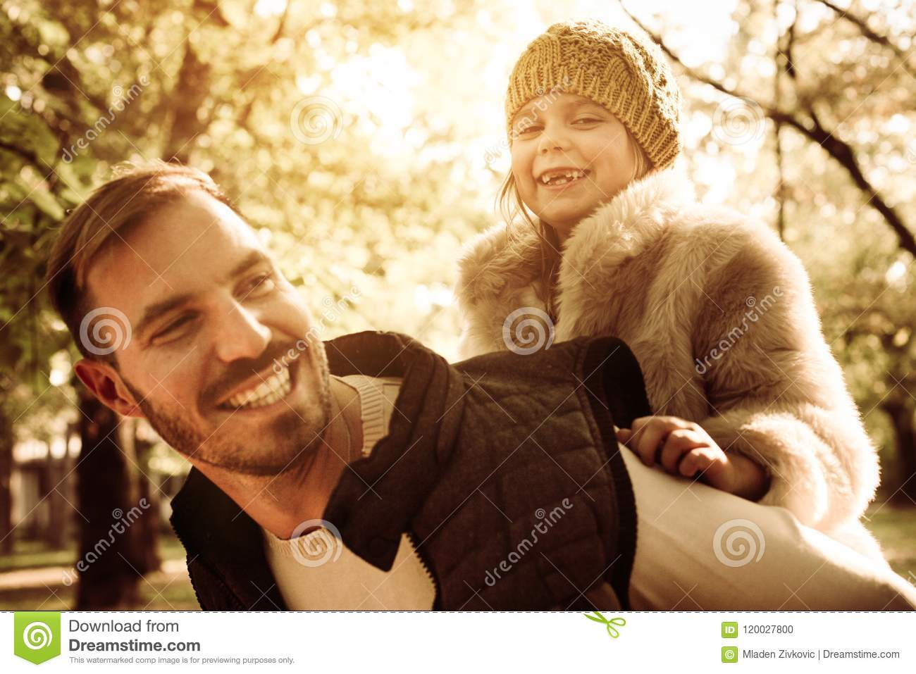 Happy father carrying his daughter on piggyback i park.