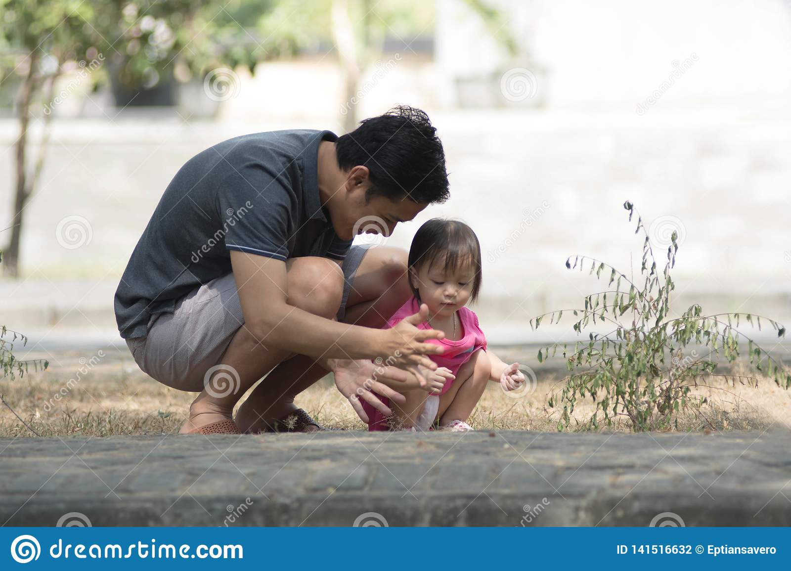 Happy father day - man and his daughter playing at park with little girl showing something to her father at sunny day