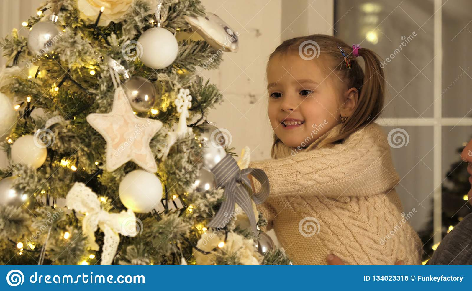 Happy father and his little daughter decorating the Christmas tree at home.